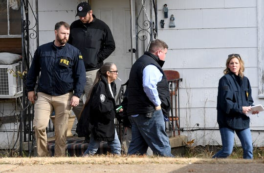 FBI agents lead Cindy McDaniel outside her old home Wednesday, Nov. 28, 2018. Evidence Response Team agents were called in to assist in the 22-year-old missing persons cold case of Cayce McDaniel by searching and collecting evidence in the home.