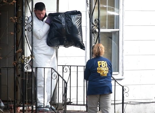 An FBI Evidence Response Team agent walks out of the old home of Cayce McDaniel in Milan with an unidentified object inside a plastic bag Wednesday, Nov. 28, 2018. Agents were called in to assist in the 22-year-old missing persons case of McDaniel by searching and collecting evidence in the home.