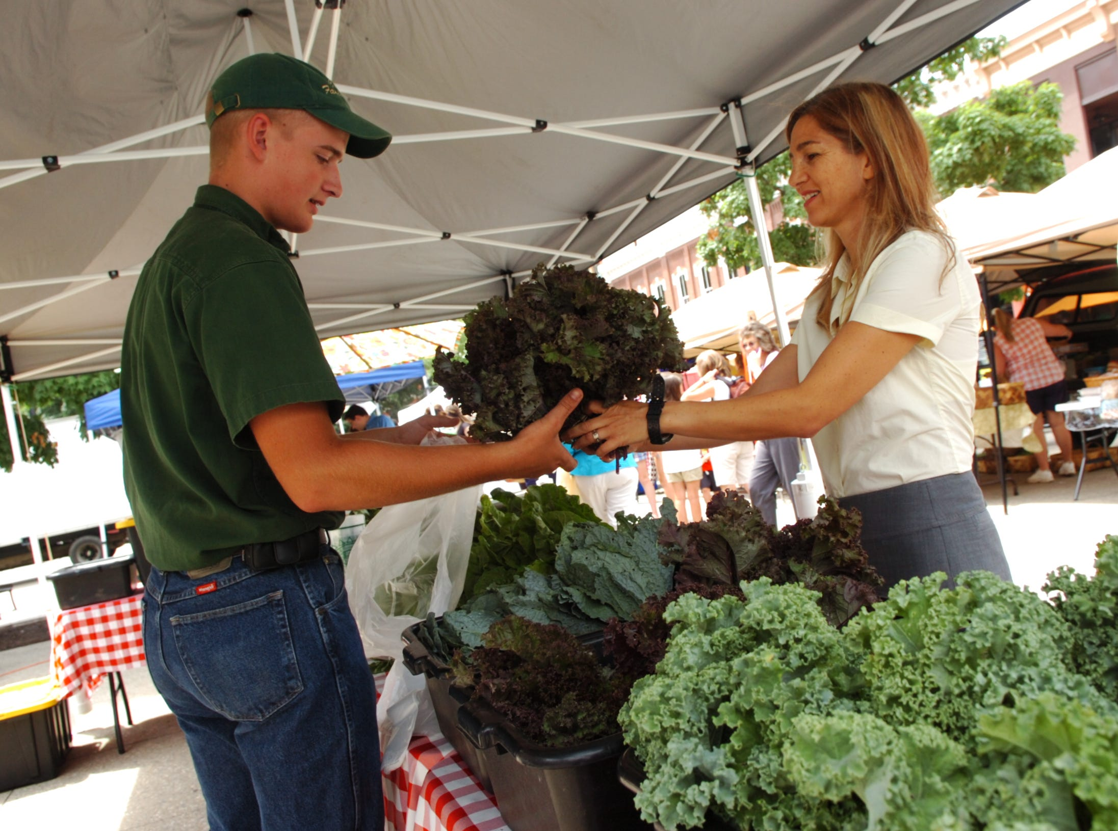 Mahasti Vafaie, owner of Tomato Head restaurants, purchases some produce from Caleb Colvin of Colvin Family Farm at the Farmers Market in Market Square on Wednesday, June 30, 2010. Vafaie opened Tomato Head 20 years ago as a lunch spot. While others have come and gone, the 46-year-old who emigrated to TN when she was 14 has over the years gradually built the Market Square restaurant into one of Knoxville's favorites serving unique, made-from scratch, locally grown food.