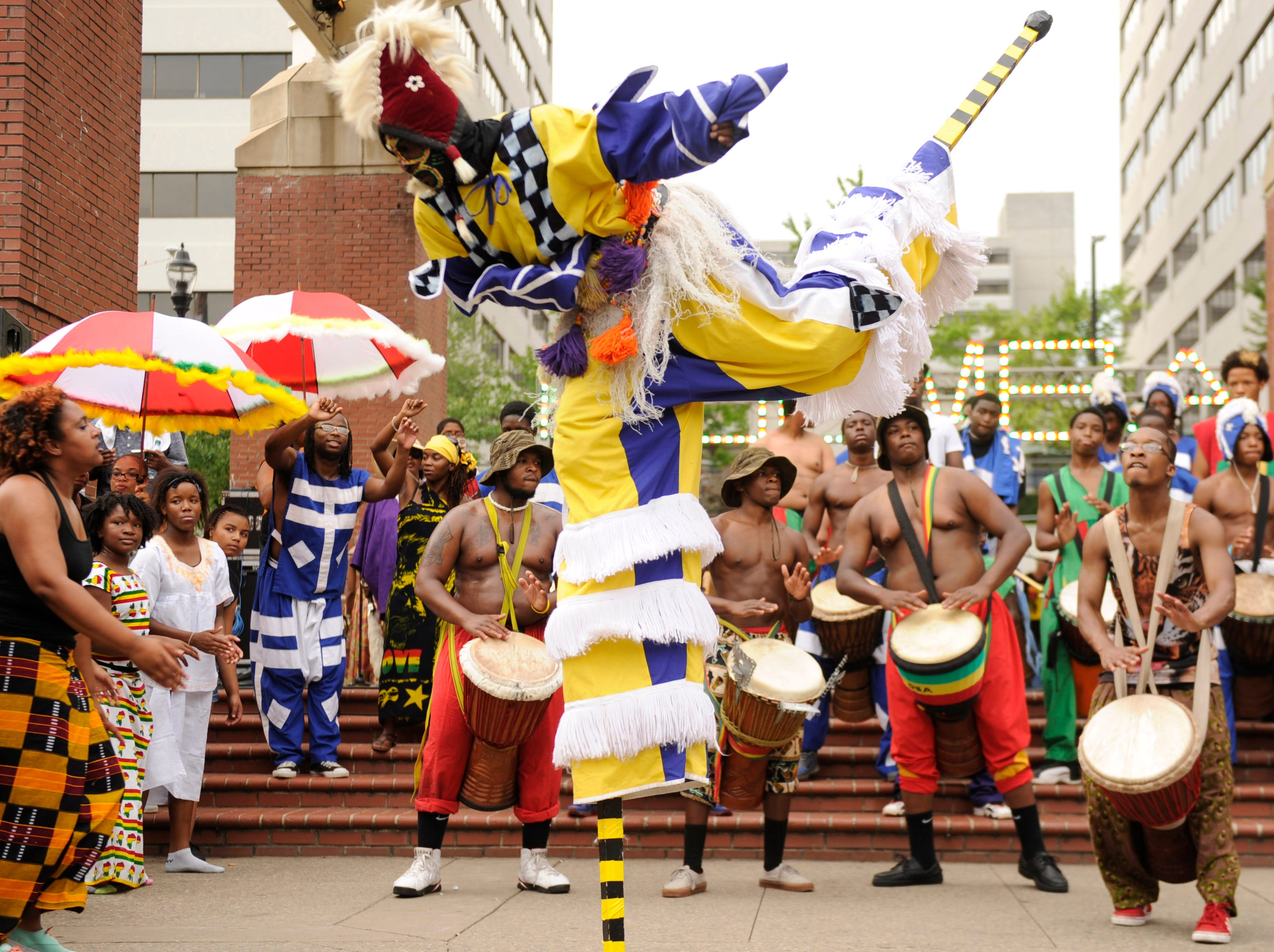 A stilt-walker balances on one leg during a performance with Kuumba Kamp drummers in Knoxville's Market Square on Friday, June 20, 2014. (ADAM LAU/NEWS SENTINEL)