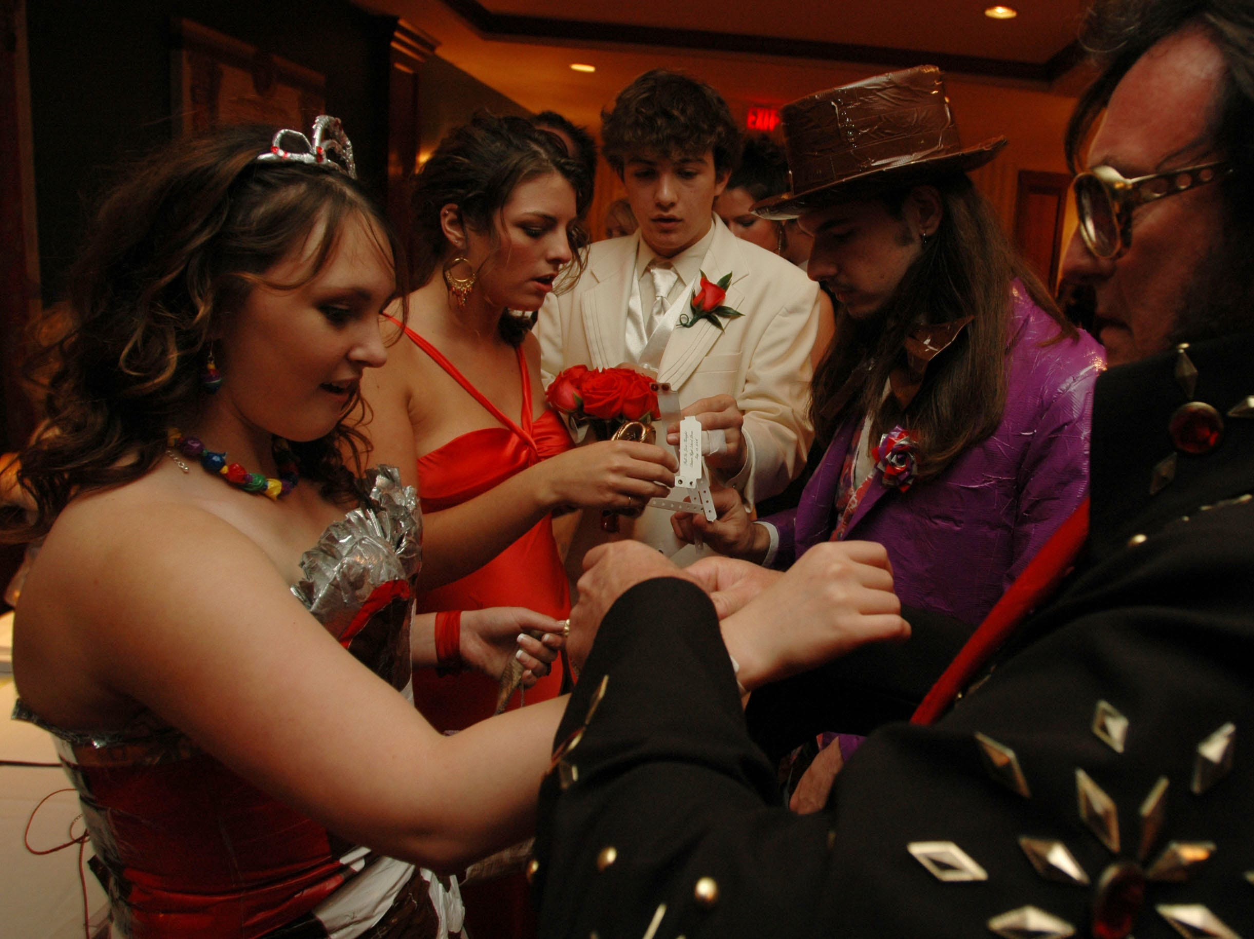 Elvis Impersonator Ray E. Robbins, right, helps Krystle Gutman, left, put her wristband on while, middle, from left, Leslie Spitzer, Dylan Ryan and T.J. Daugherty help eachother fasten their wristbands while entering the Clinton High School Prom at the Crowne Plaza Hotel in Knoxville, Tenn., Saturday night. -05/13/2006.