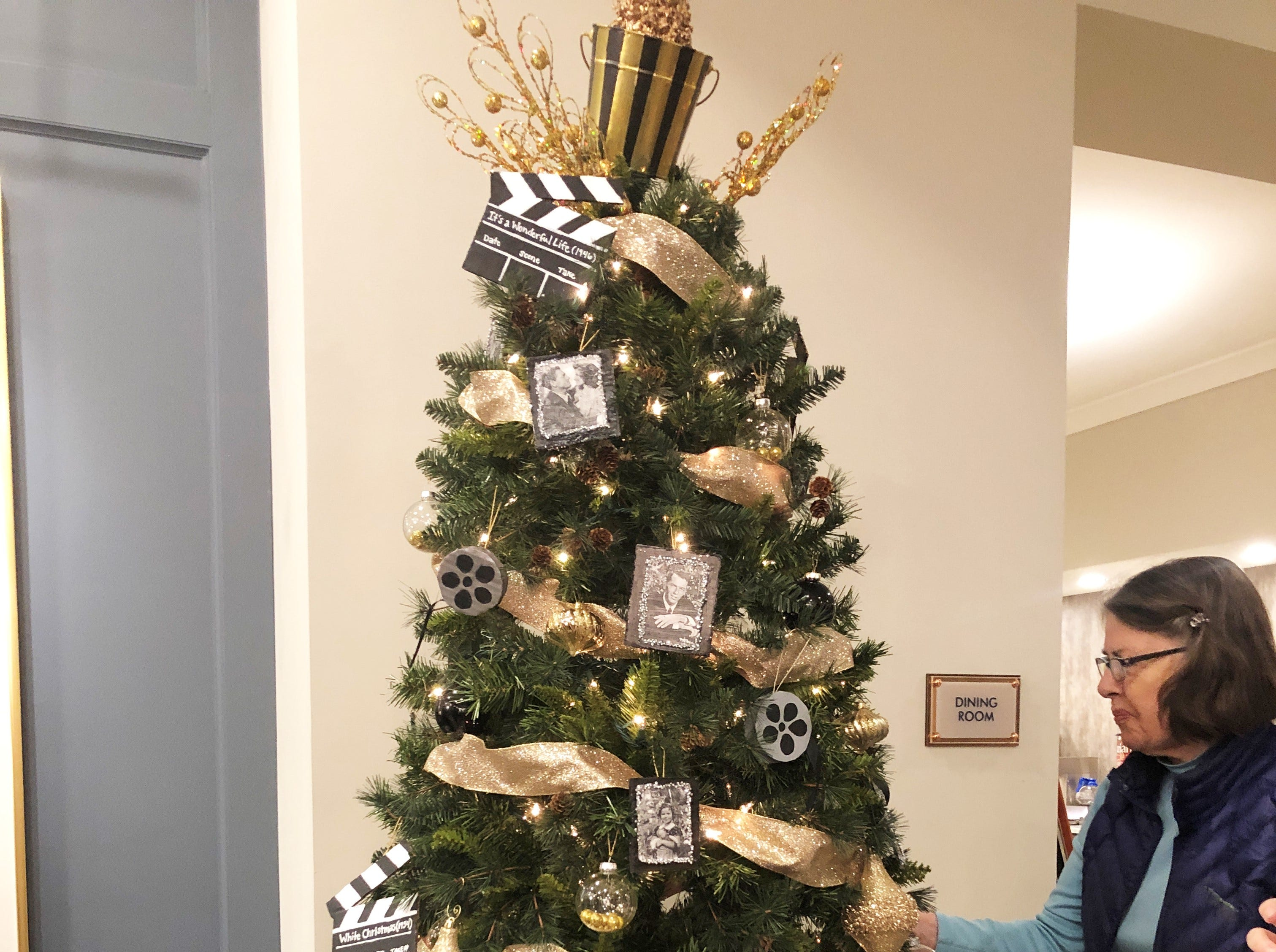 A resident at Knoxville High Independent Senior Living takes a closer look at the tree decorated by Halls Art Club.