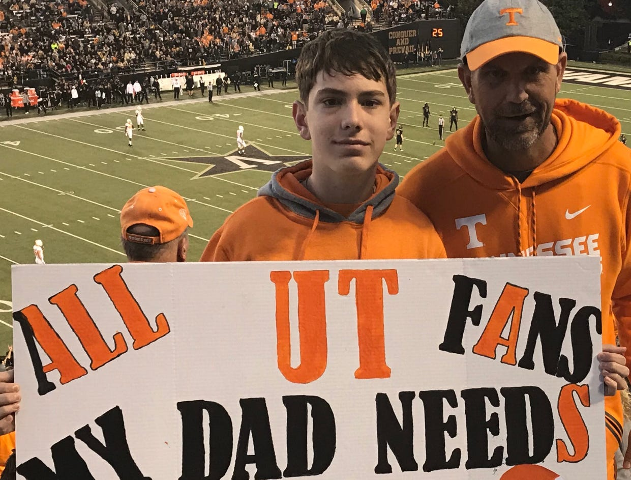 Travis Fuller, right, and his son Preston display a sign with a plea for a kidney at the Tennessee-Vanderbilt football game. The social media post with this photo went viral.