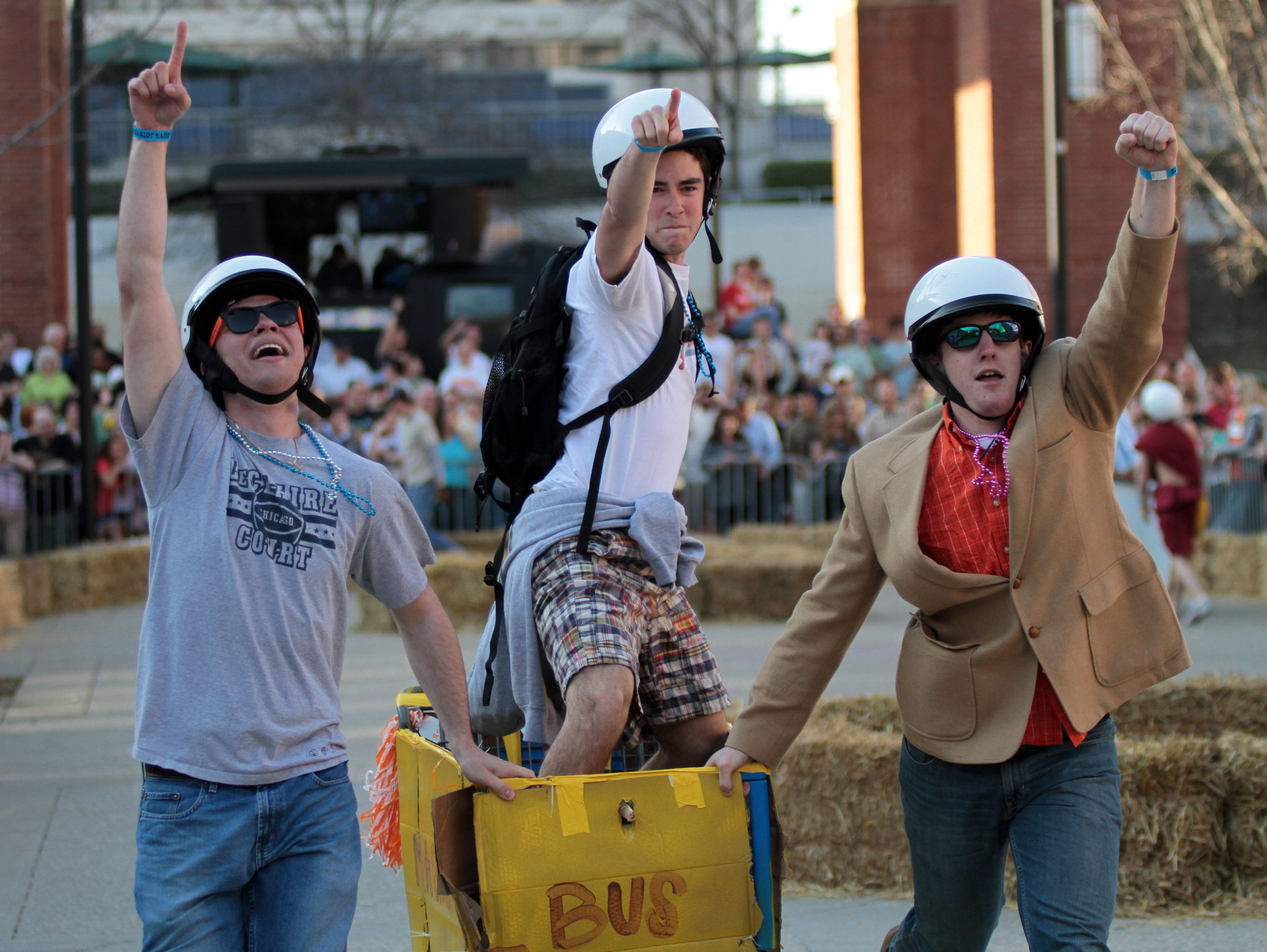 Team Magic School Bus, from left, Ross Rowland, Adam Roddy and Sovica Djurdjevic come across the finish line on Saturday, March 27, 2010 during the Red Bull Chariot Race on Market Square.