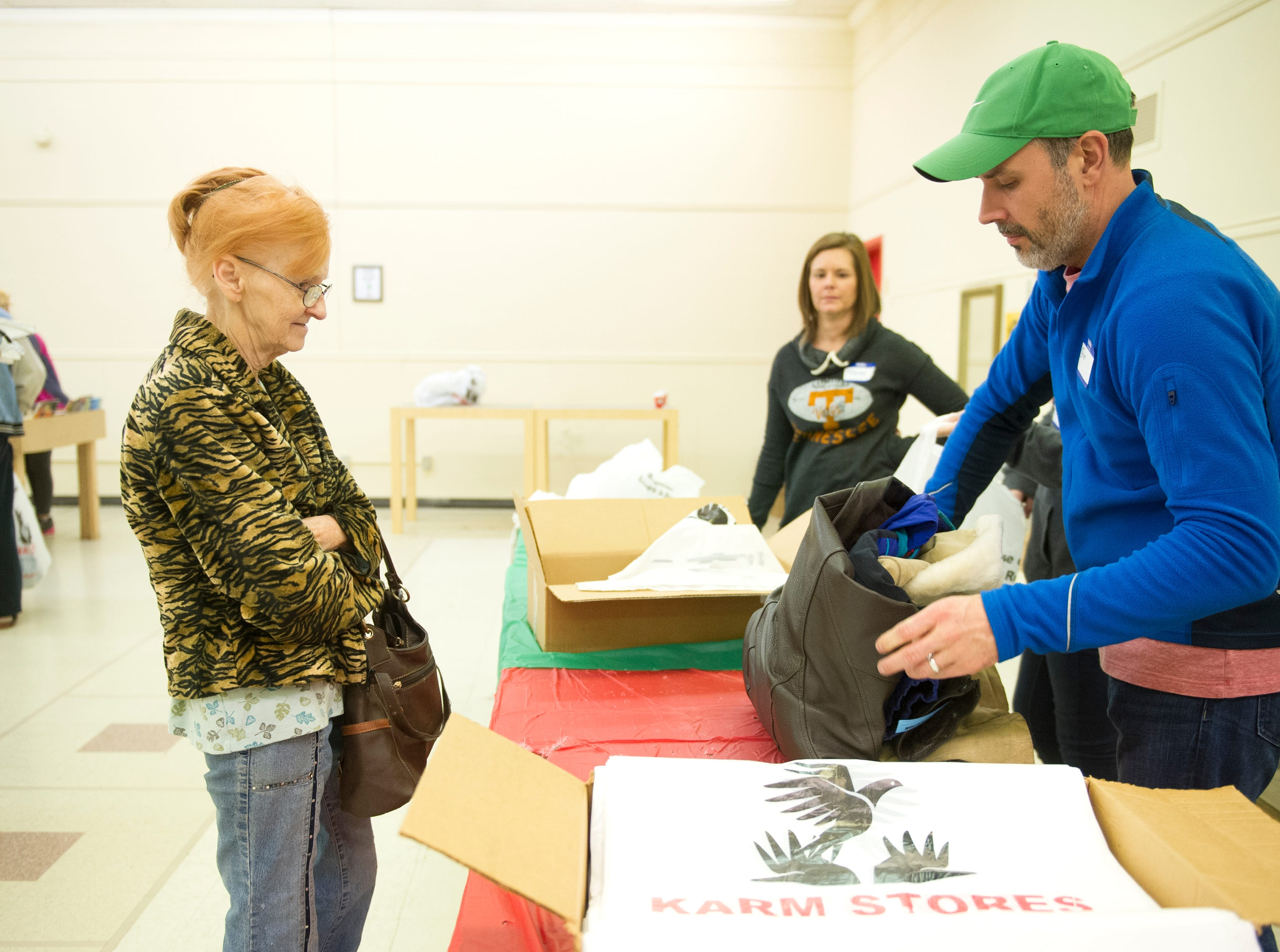 Janice Staton of Knoxville (left) waits as Volunteer Brian Mason wraps her coats up during KARM's 30th annual Coats for the Cold coat drive in Knoxville Saturday, Dec. 5, 2015.