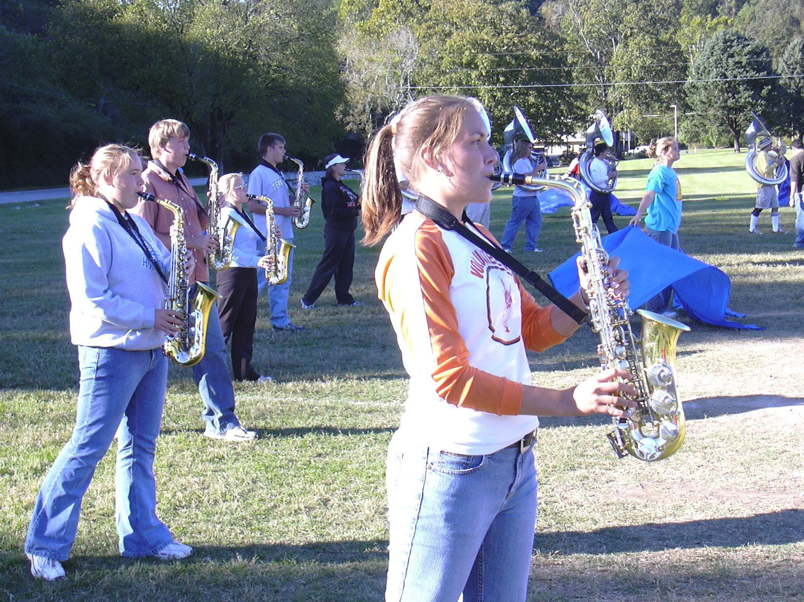 Anna Baker, foreground,Êplays the saxophone while participating in drills in preparation for the latest halftime show by members of the Clinton High School Marching Band. In back, from left: Rachel Stonecipher, Cory Glen, Melissa Gingery, Brian Long and Kelly Coffman. Twirling the flags at right is Jill Ferrie.  2003.