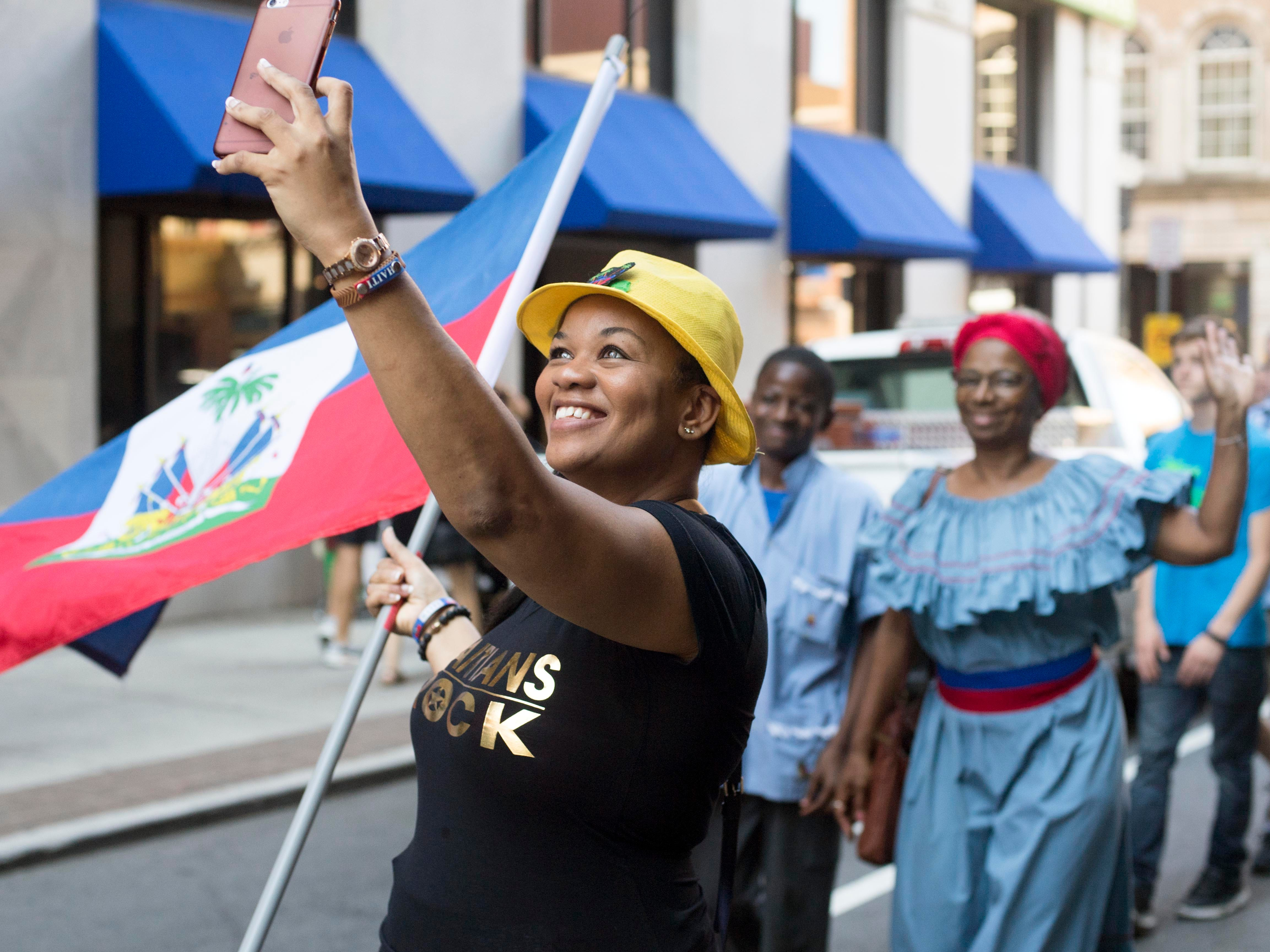 Stephanie Hall photographs herself with the Haitian flag and is participating in the HoLa Festival's Parade of Nations at Market Square on Sunday, September 30, 2018.