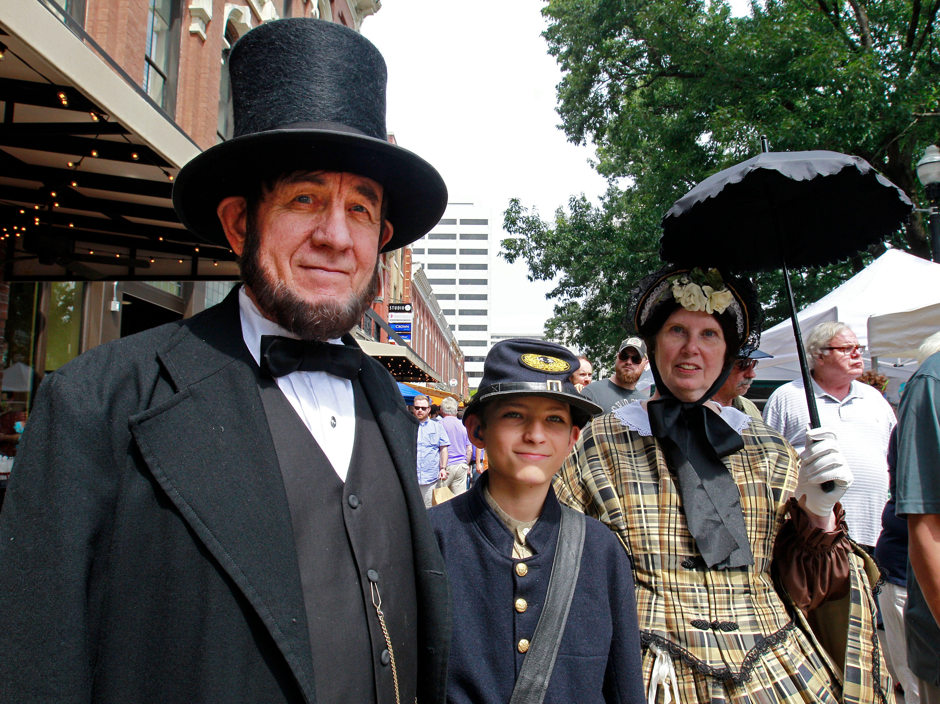 "Tom ""Abraham Lincoln"", left, along with his son Kyle, center, and wife, Sue ""Mary Lincoln"" Wright, walk along Market Square during History Day festivities downtown Saturday, August 16, 2014 in Knoxville, Tennessee. (Photo by Wade Payne, Special to the News Sentinel)"