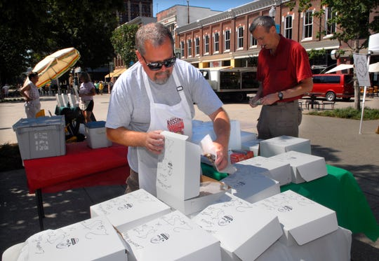 Bakery goods vendor Dave Gwin, left, fills an order for customer Mark Hall at the Market Square Farmers' Market, Wednesday. The historic square was originally donated to the city 150 years ago to provide space for an open-air market so area farmers could sell their produce directly to the public.  6/6/2007
