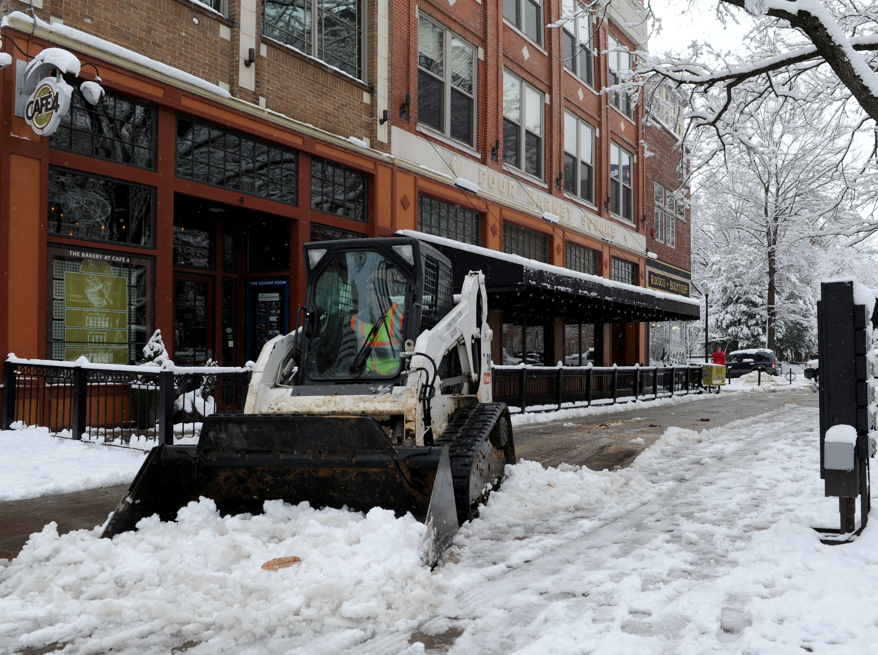 City of Knoxville public grounds maintenance workers use machinery to remove snow from sidewalks in Market Square in downtown Knoxville on Thursday, Feb. 13, 2014. The winter storm on Wednesday brought six inches of snow to the Knoxville area. (AMY SMOTHERMAN BURGESS/NEWS SENTINEL)