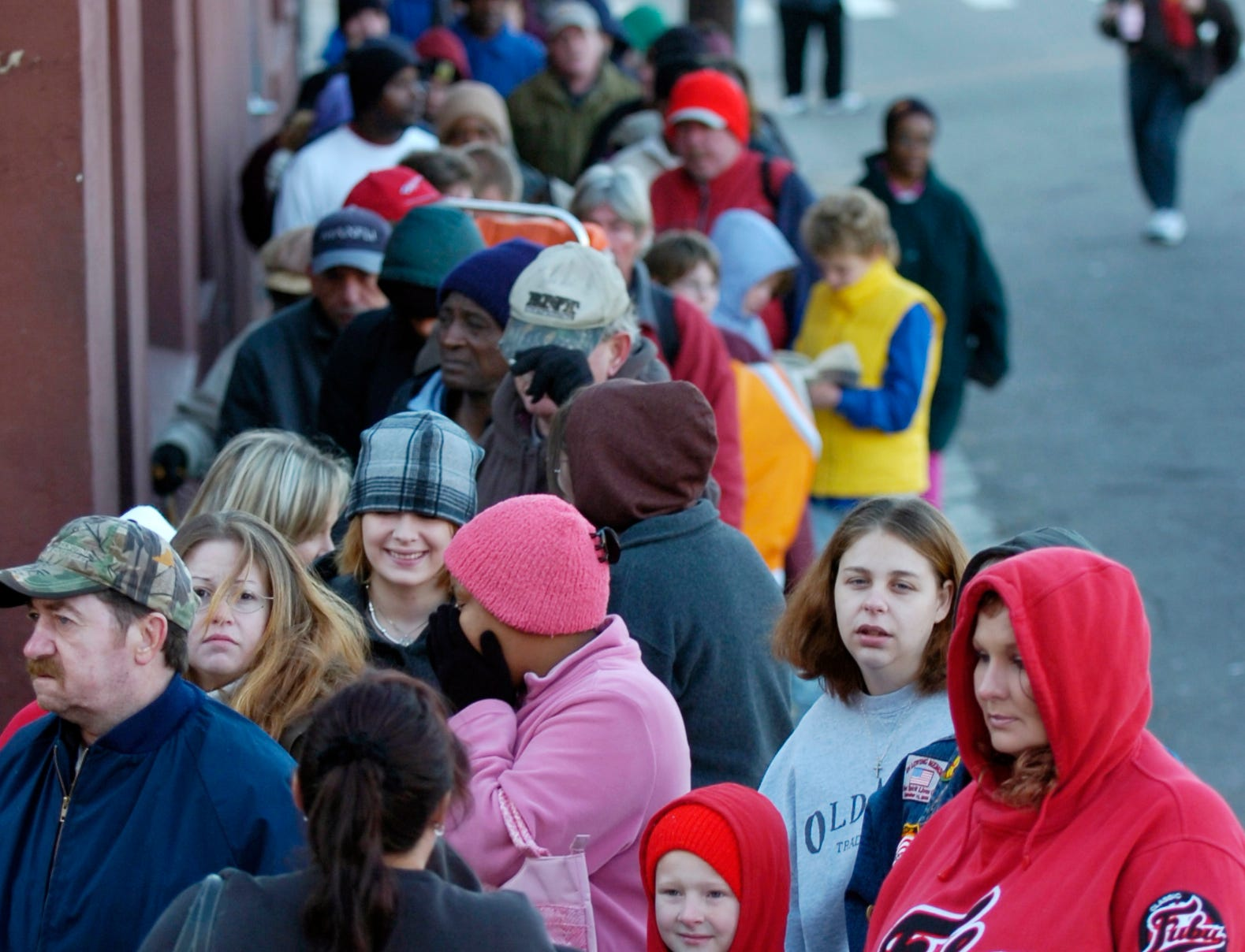 Eight year-old William Fillicetti, center, a third grade student at West View Elementary School, waits in line for a new coat during the 21st annual Coats for the Cold distribution on Saturday at the Knox Area Rescue Ministries. William and his mother, Kim, right, had to wait about an hour for a new coat before leaving for Gatlinburg to watch the Christmas parade according to Kim Fillicetti.