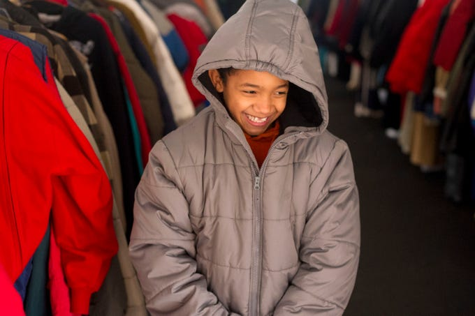 Jebri Taylor, 8, smiles as he tries on a new coat he picked out during Knox Area Rescue Ministries' Coats for the Cold event on Saturday, December 1, 2012. According to KARM president, Burt Rosen, approximately 2000 will be given away during the annual event.
