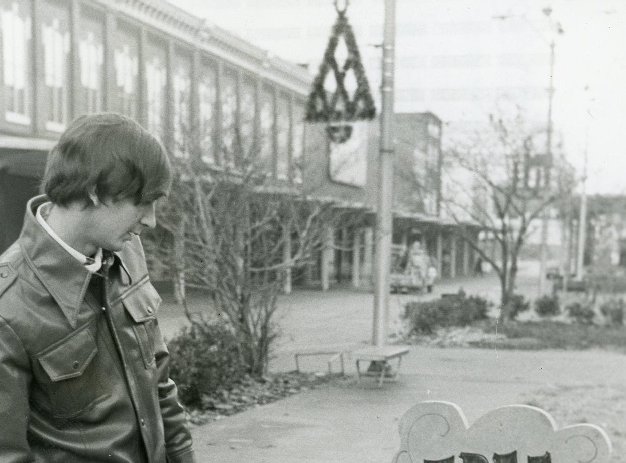 "Brad Day reads a sign on Market Square Mall, December, 1978. The sign reads ""A tree will return to this spot for your divine pleasure."""