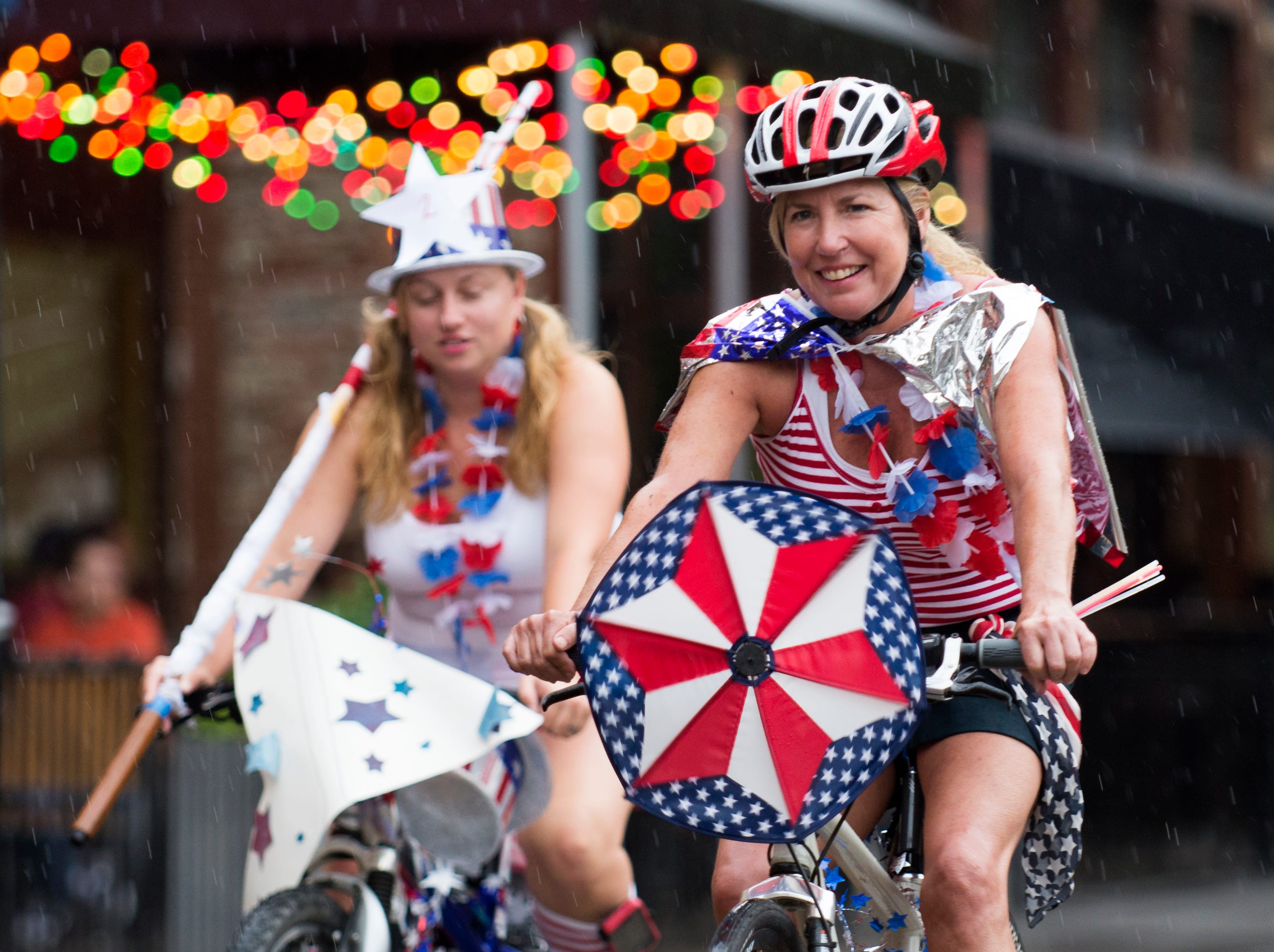Cecilia Petersen rides with a whirlygig during a Patriotic Bike Parade Thursday, June 26, 2014, at Market Square. Sponsored by the city's Office of Special Events, the rain-shorten parade attracted dozens of riders in red, white, and blue. (PAUL EFIRD/NEWS SENTINEL)