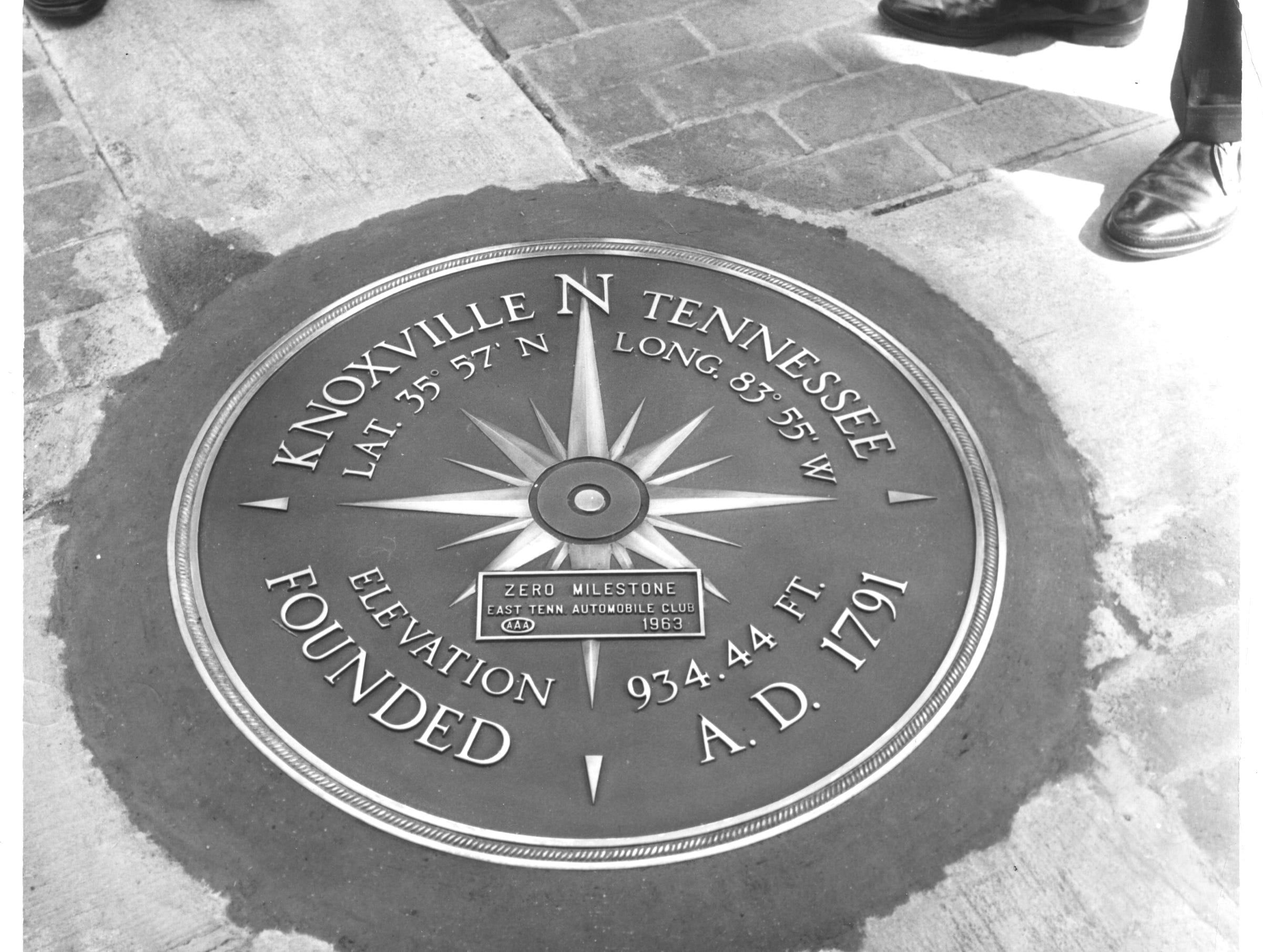 "in this 1963 photograph, men stand around the newly-installed zero milestone marker in Knoxville's Market Square. Used by the American Automobile Association (AAA) at the marker that denotes the ""center"" of Knoxville for mapping and driving purposes. The marker may have been removed during one of the renovations of the downtown area."