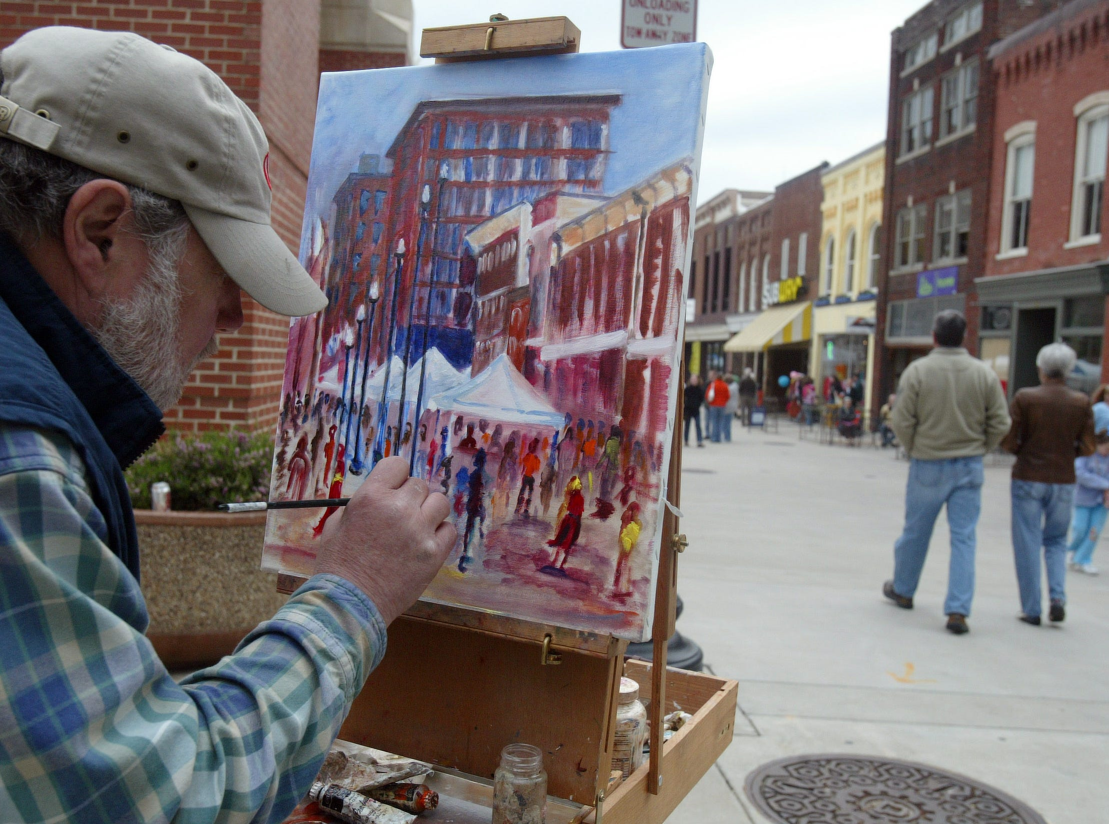Local artist Brad Selph finishes up his view of Market Square during the Knoxville Opera's Rossini Festival held Saturday. The event features opera performances, wine tasting, artists and plenty of Italian food.  04/08/06