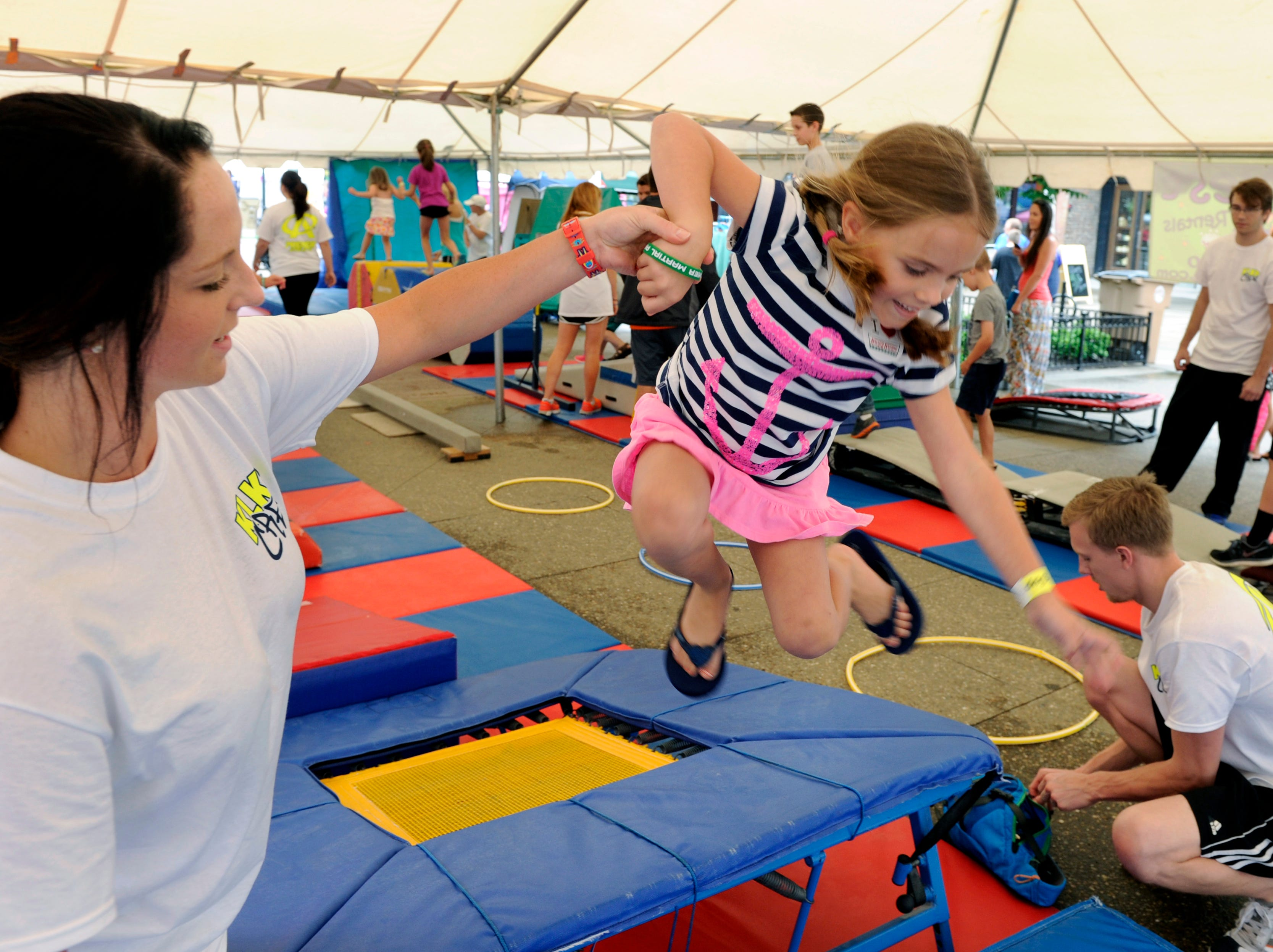 Alli McKamey, 6, gets a hand from Premier Athletics employee Charlotte Loy while playing at Knoxville's Largest Kids Party on Market Mall Friday, Jun. 13, 2014.    (MICHAEL PATRICK/NEWS SENTINEL)