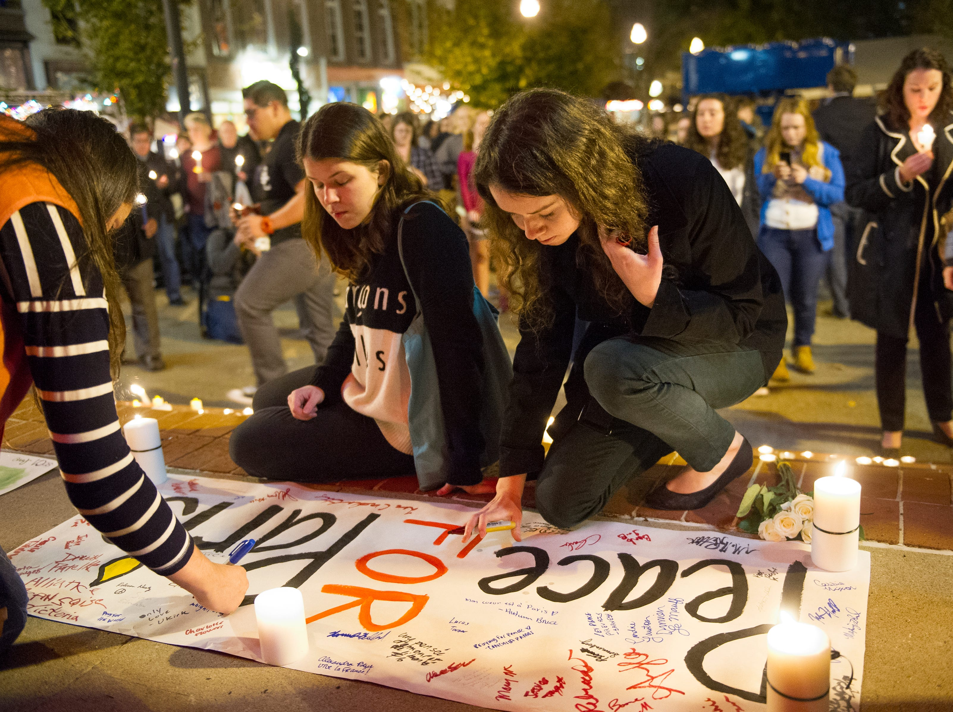 "Michelle Johnson of Johnson City (right) signs a banner that reads ""Peace for Paris"" during a vigil held for victims of the recent shootings in Paris hosted by the University of Tennessee student French honor society, Pi Delta Phi in Market Square Tuesday, Nov. 17, 2015. (JESSICA TEZAK/NEWS SENTINEL)"