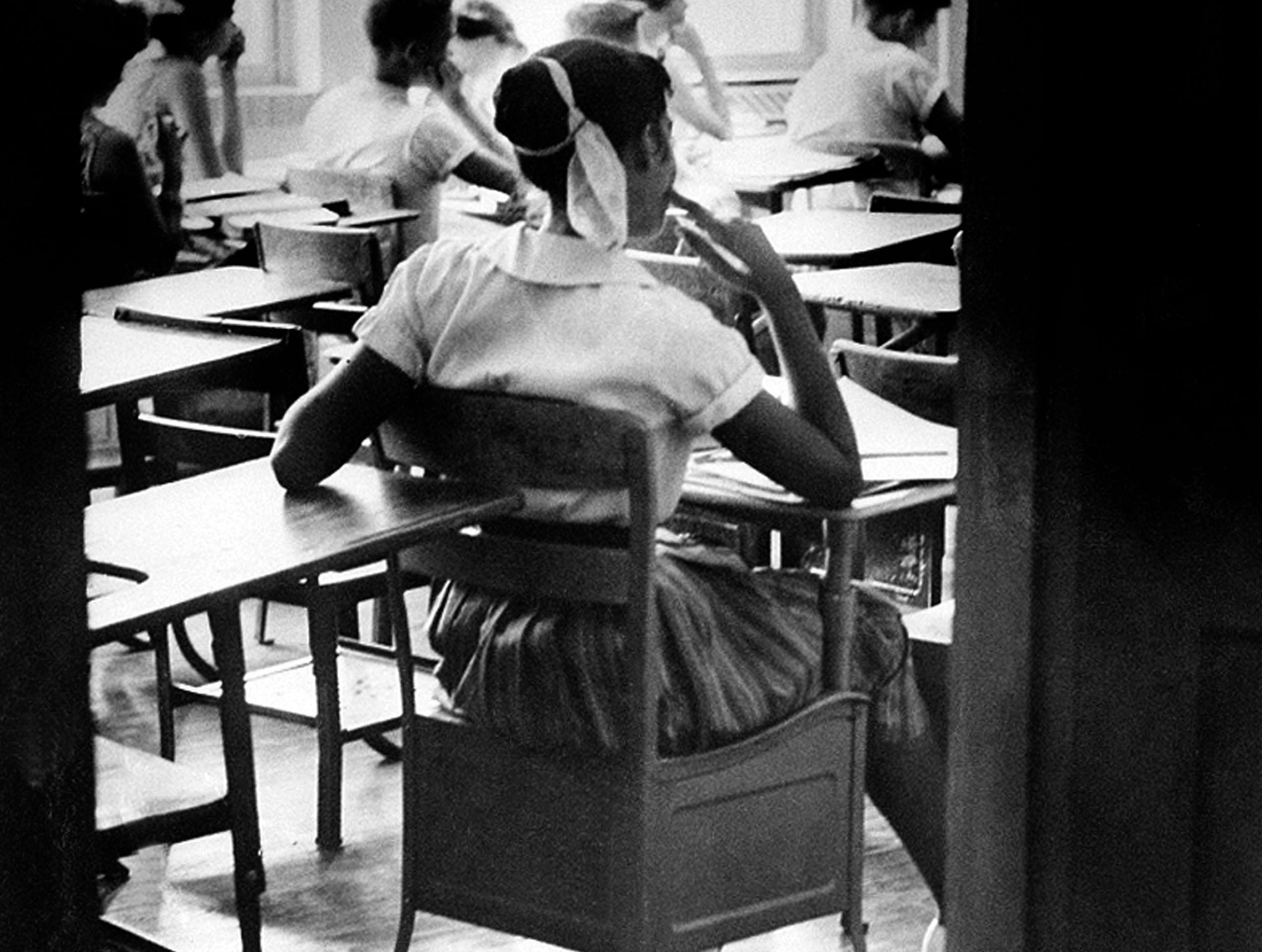 "An unidentified black student is shown in this Aug. 31, 1956, file photo sitting inside a classroom at the newly integrated Clinton High School in Clinton, Tenn. She sits in a rear seat, separated by empty desks from her white classmates. She is one of 12 blacks under court order to integrate the school of about 800 whites. They became known as the ""Clinton 12."""