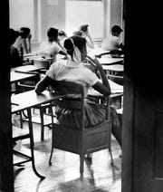 """An unidentified black student is shown in this Aug. 31, 1956, file photo sitting inside a classroom at the newly integrated Clinton High School in Clinton, Tenn. She sits in a rear seat, separated by empty desks from her white classmates. She is one of 12 blacks under court order to integrate the school of about 800 whites. They became known as the """"Clinton 12."""""""