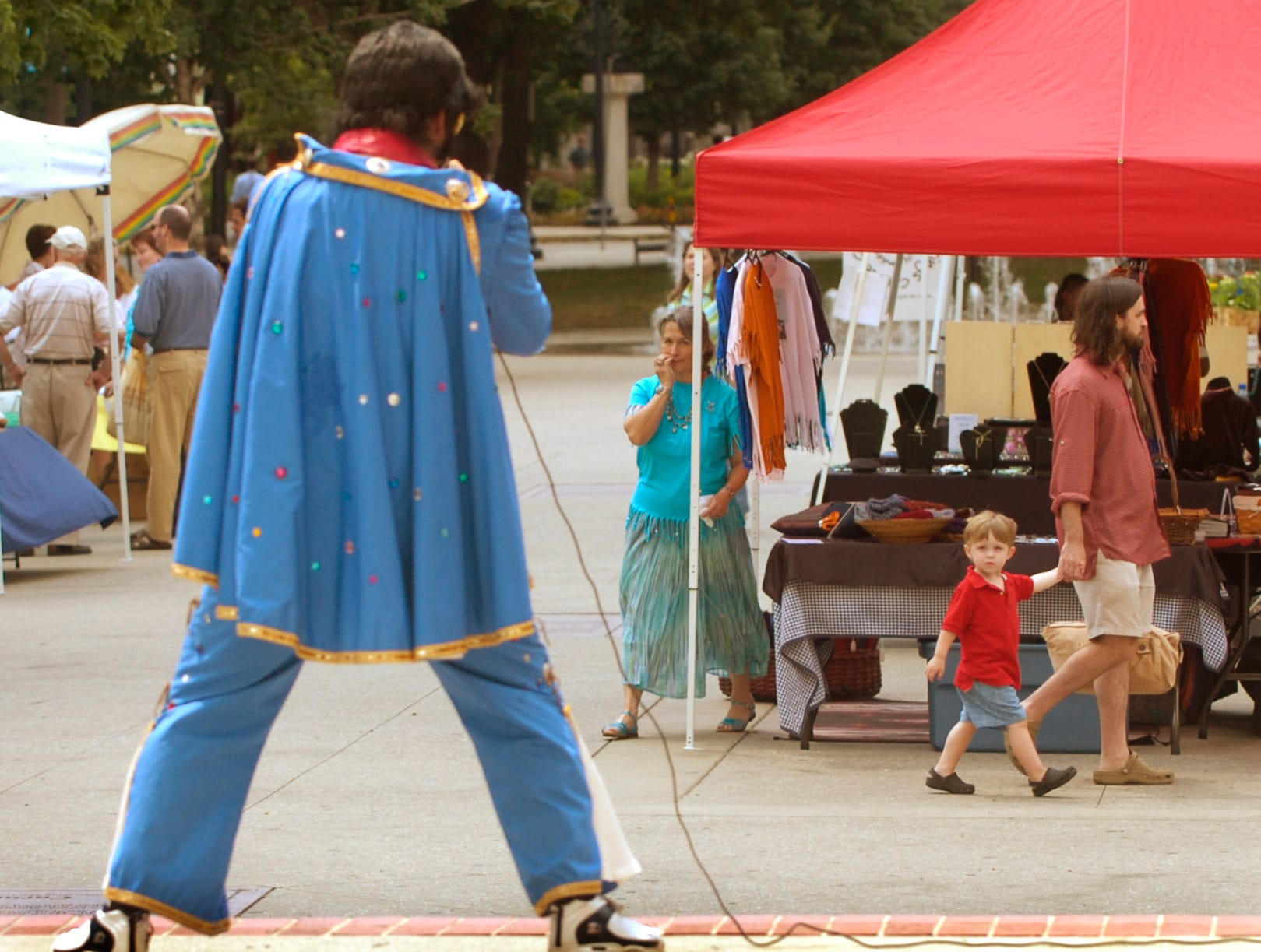 While walking with his father Darrien Thomson (cq), right, Hayden Brackeen, 2, looks on as Elvis impersonator Jeff Martin performs Wednesday at the Market Square Farmers' Market. Martin has become a regular to the market.  6/6/2007