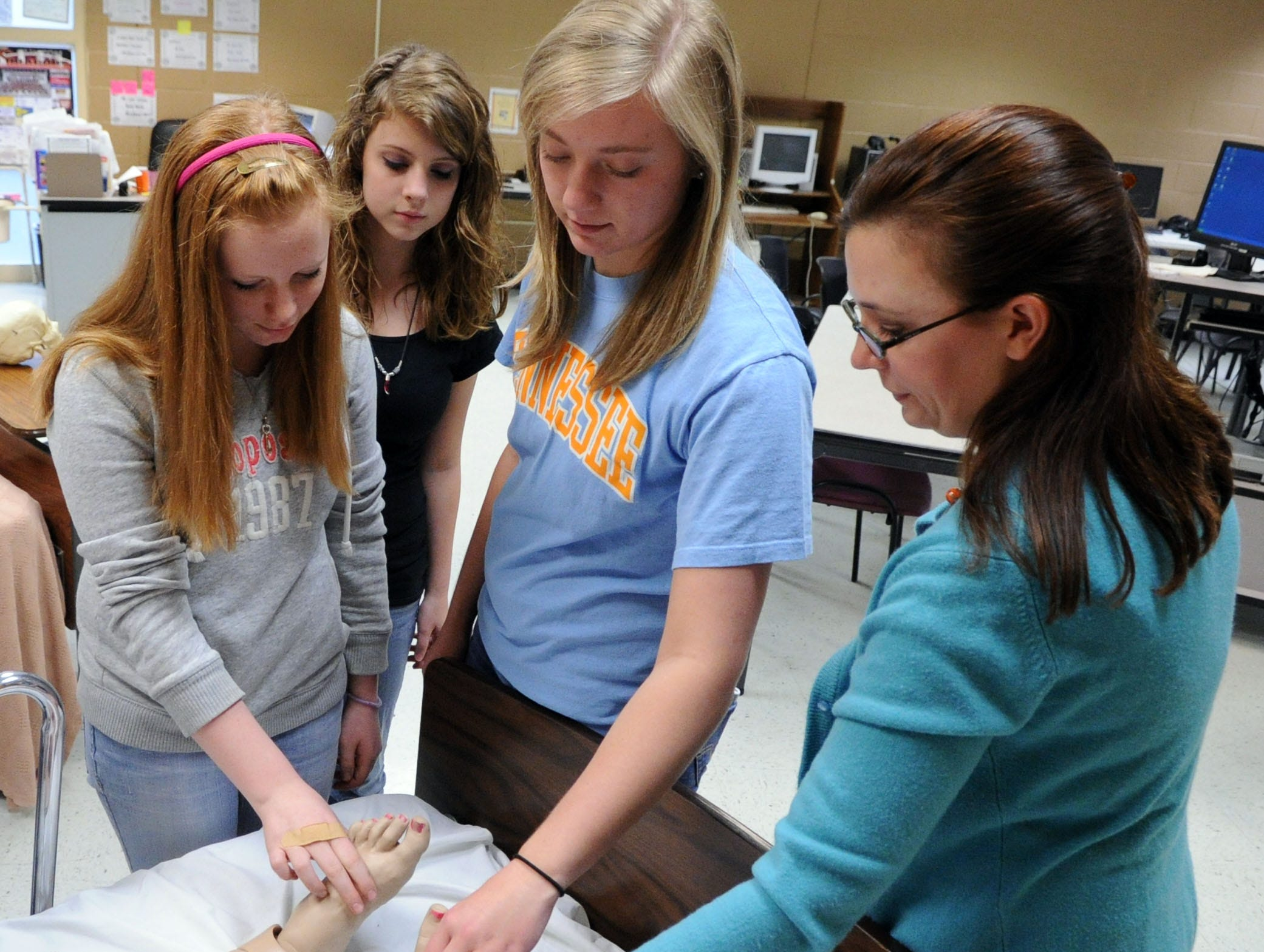 Kayla Norman, Morgan Russell and Kennedy Hancock, left to right, look on as teacher April Freeman gives instructions in her medical therapudics class at Clinton High School in Clinton, Tenn., March 31, 2011.