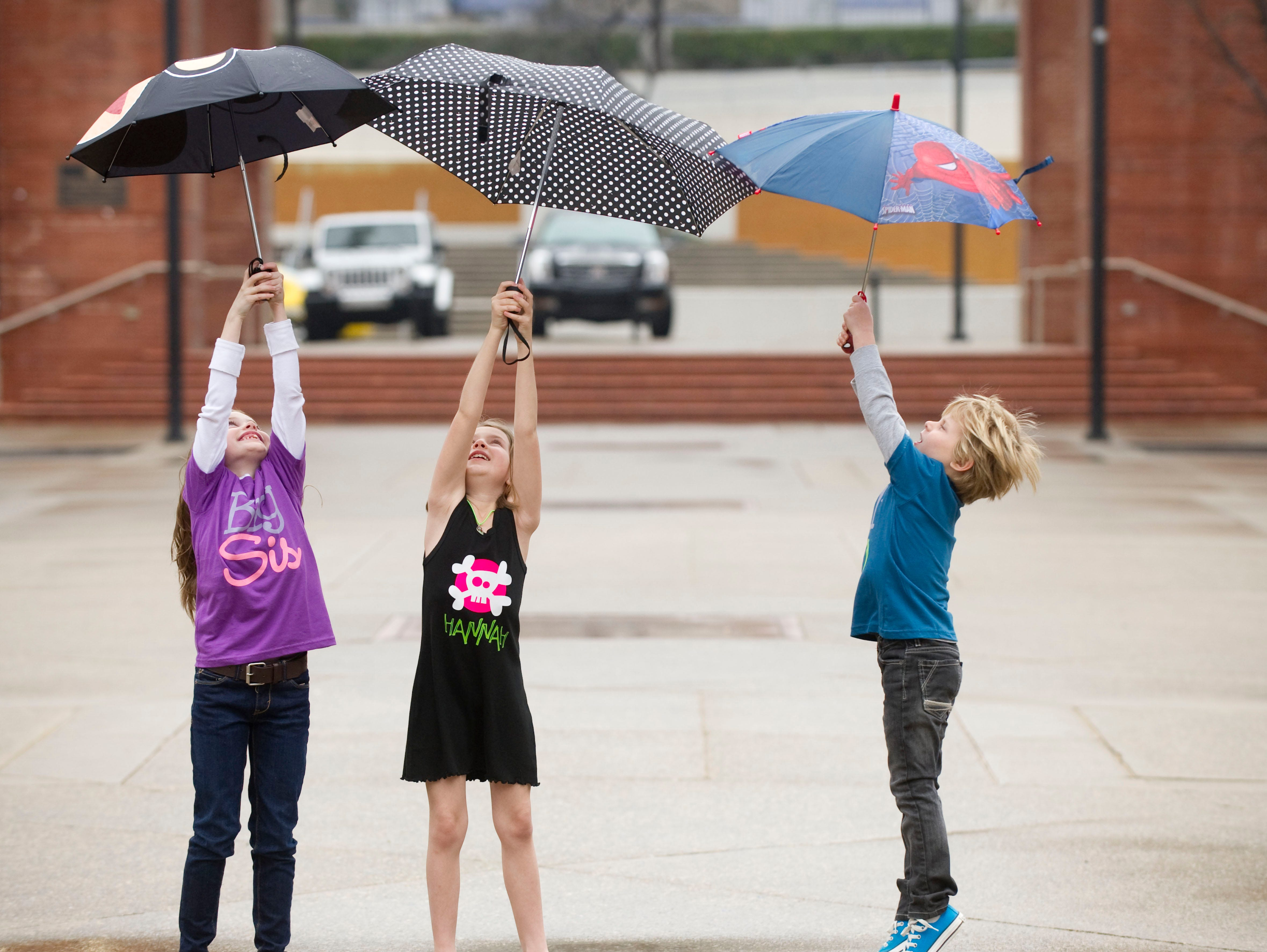 From left, Ella Gozdieski, 7, Josie Wells, 8, and, Chase Gozdieski, 8, all of Gage Talent, play in Market Square in shirts by EM Tanner Designs.