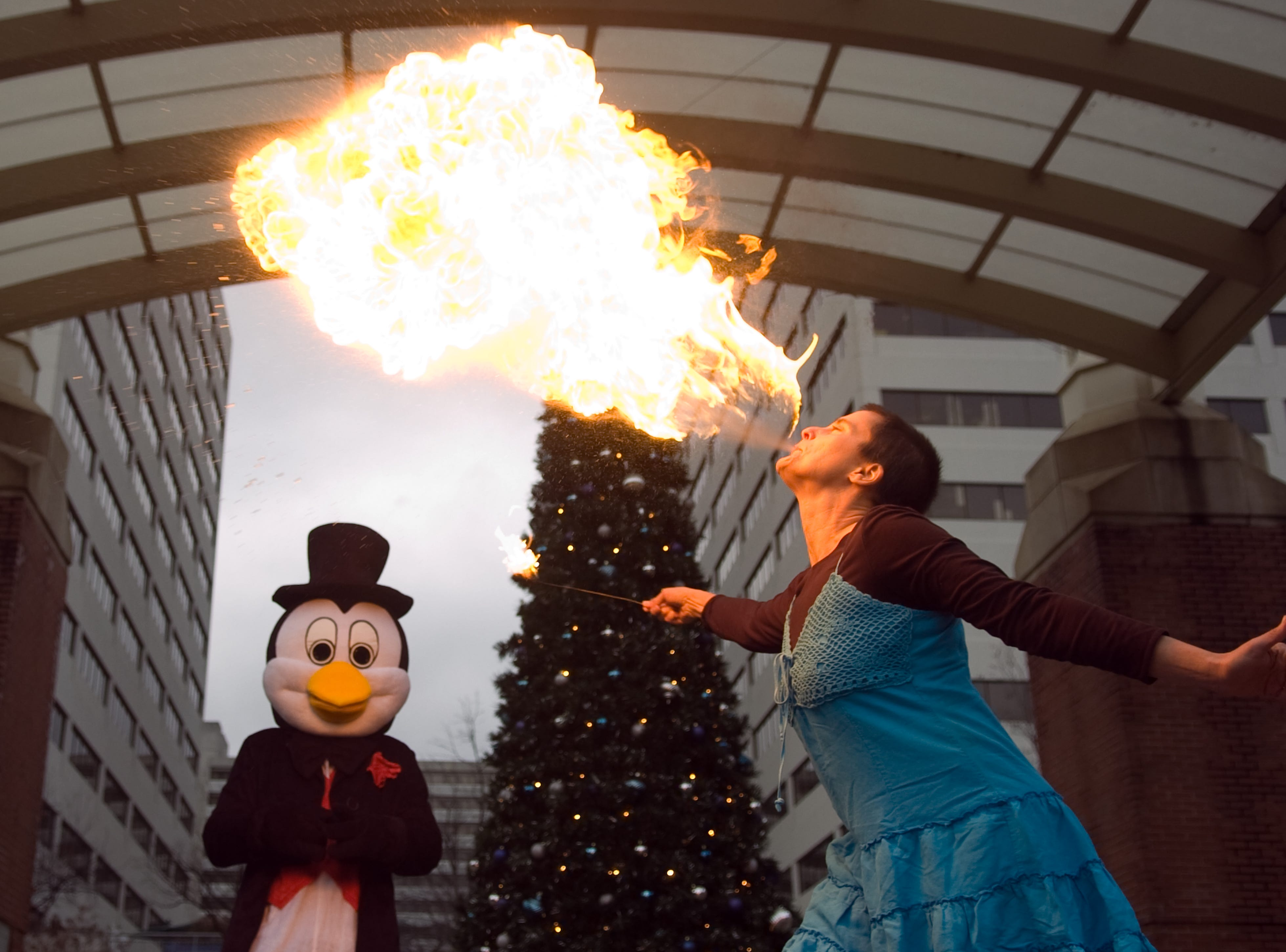 Lissa McLeod gives a demonstration on fire breathing at the Market Square stage on Monday, Nov 30, 2009. With McLeod is   Holidays on Ice mascot, Jello. The two are guests  during a press conference announcing Market Square's new year's eve celebration, First Night Knoxville.