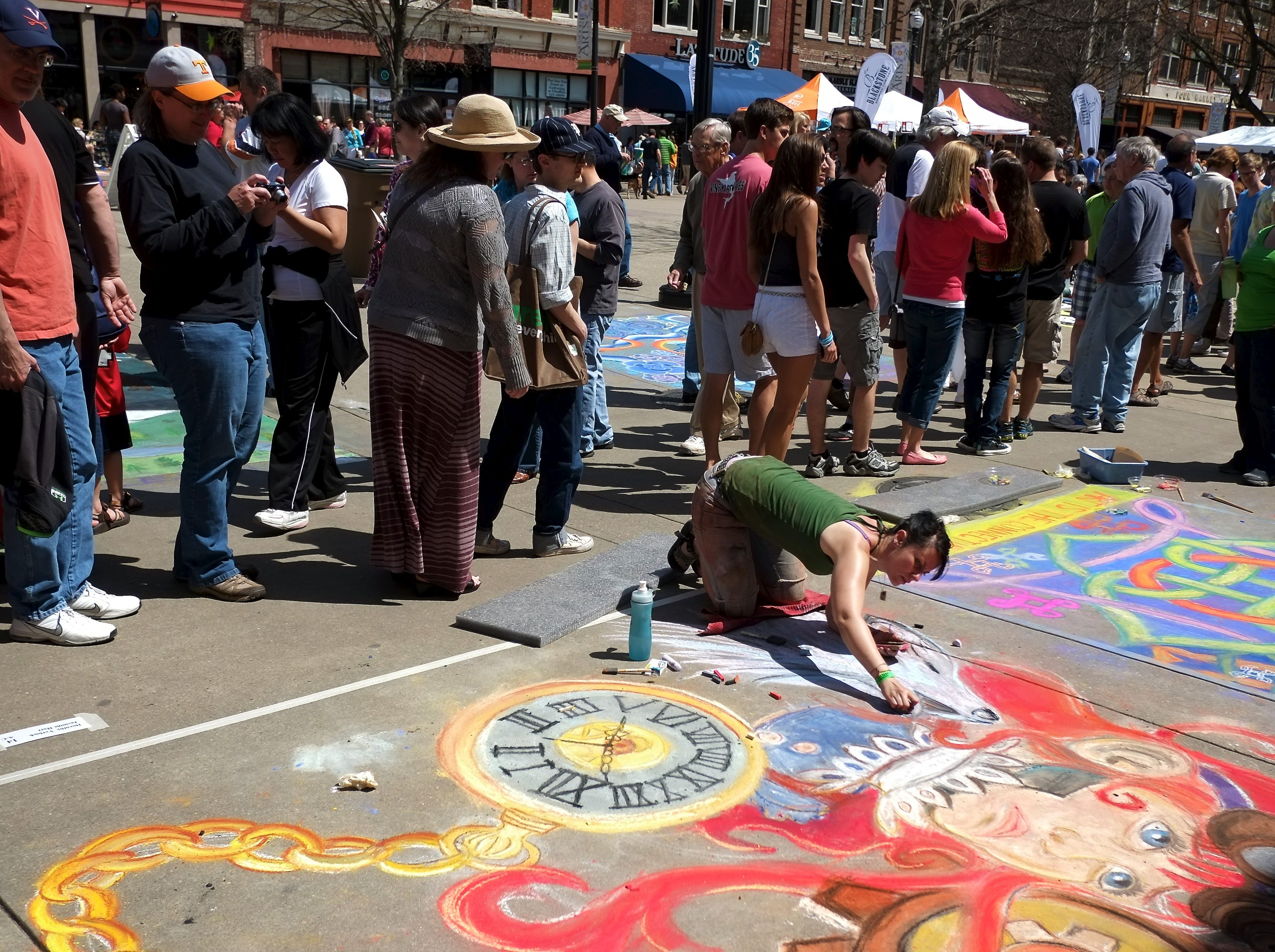 Dorothy Verbick, center front, works on a chalk drawing during the 5th annual Chalk walk on Saturday, April 6, 2013 as part of the Dogwood Arts Festival on Market Square. 100 chalk drawings were created by more than 150 artists. (Chad Greene/Special to the News Sentinel)