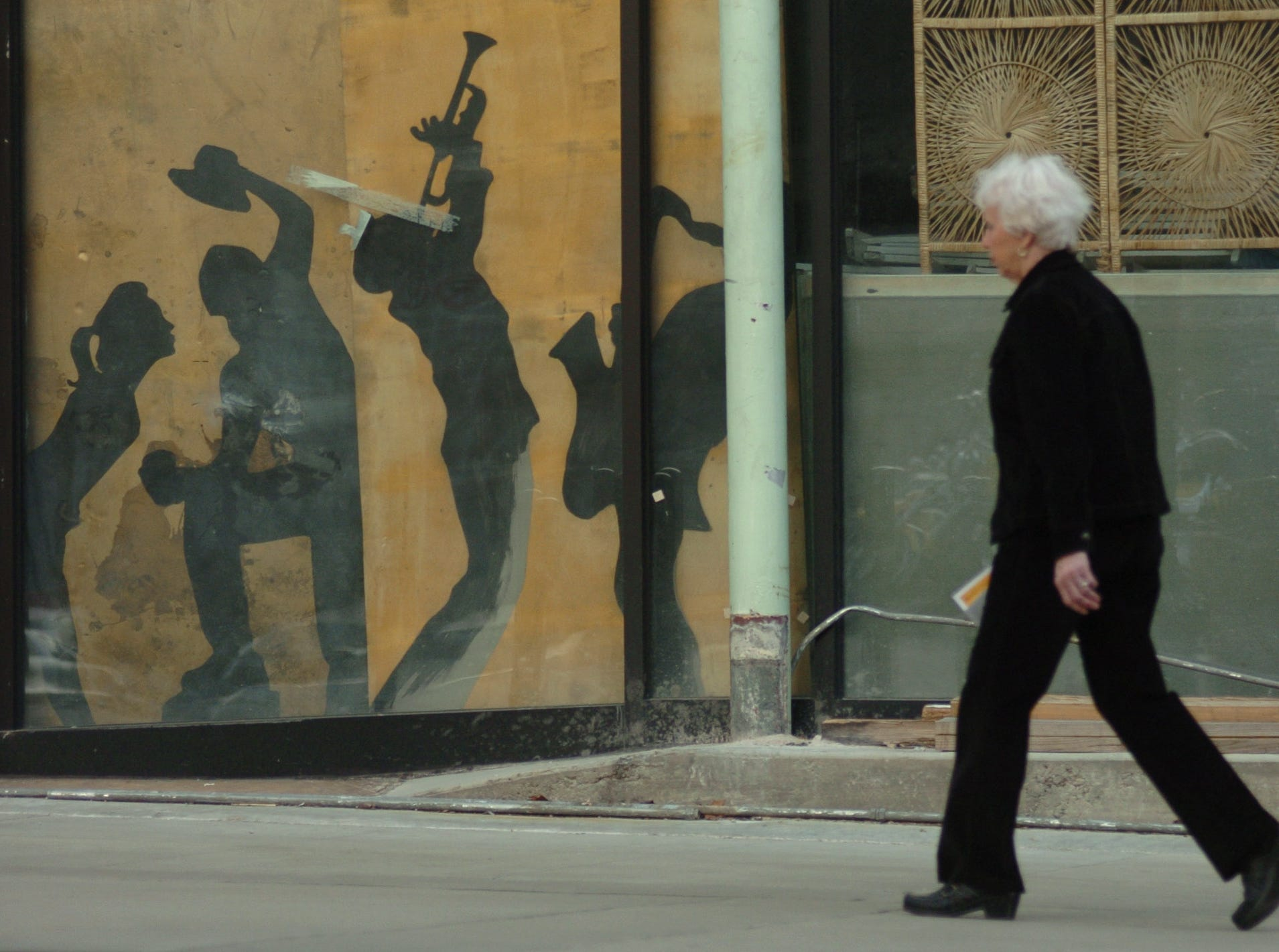 Marilyn Dew walks past some painted silhouettes of figures dancing and playing music, reminiscent of a Mardi Gras scene, on Market Square Tuesday afternoon, which is officially Mardi Gras day, in downtown Knoxville, Tenn. Dew was visiting her daughter, Susie Dew, who owns World Grotto on Market Square. The figures were in the window of a building being rennovated. Jeff Adkins/NEWS SENTINEL ----02/28/2006.
