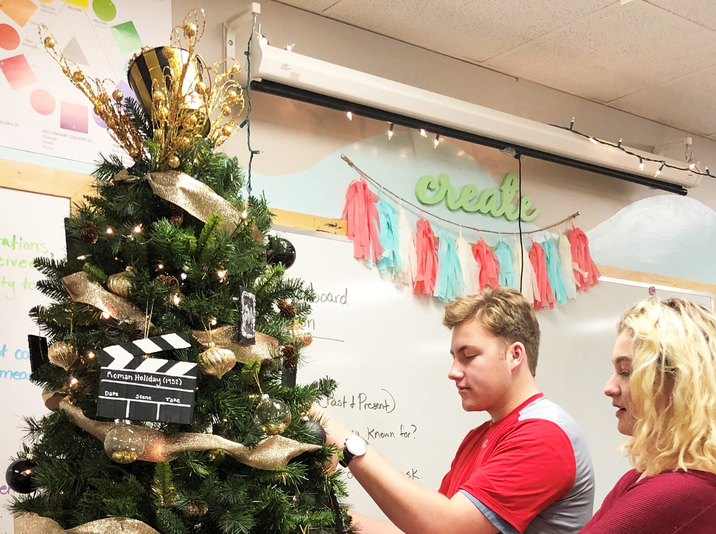 Seniors Elizabeth Meyers and Harrison Campbell inspect the tree to decide on any last last-minute tweaks. Meyers particularly likes the hanging pictures with the glitter around the edge, while Campbell liked the creation aspect of the project and the chance to work together.