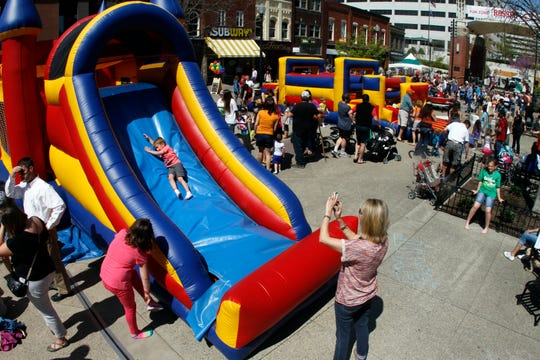 A child slides down as other play at the Fun Zone during the annual Rossini Festival Saturday, April 12, 2014 on Market Square.