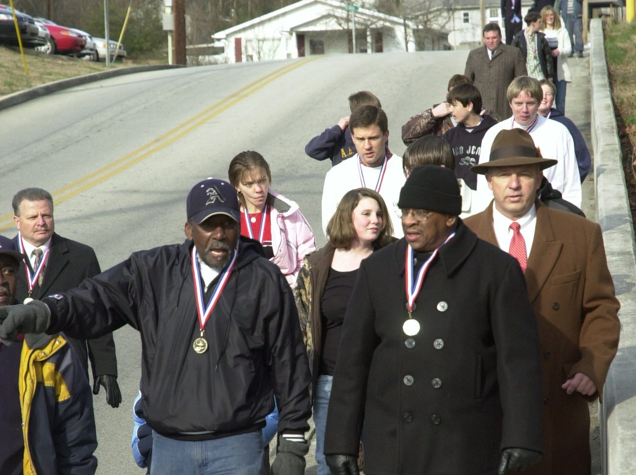 "Alfred Williams, left, recalls a memory from the days 50 years ago when he was one of the original ""Clinton 12"" who became the first black students to integrate formerly all-white Clinton High School. Also pictured in front during Friday morning's reenactment of those walks is another member of that group, Bobby Cain.  Feb. 10, 2006"