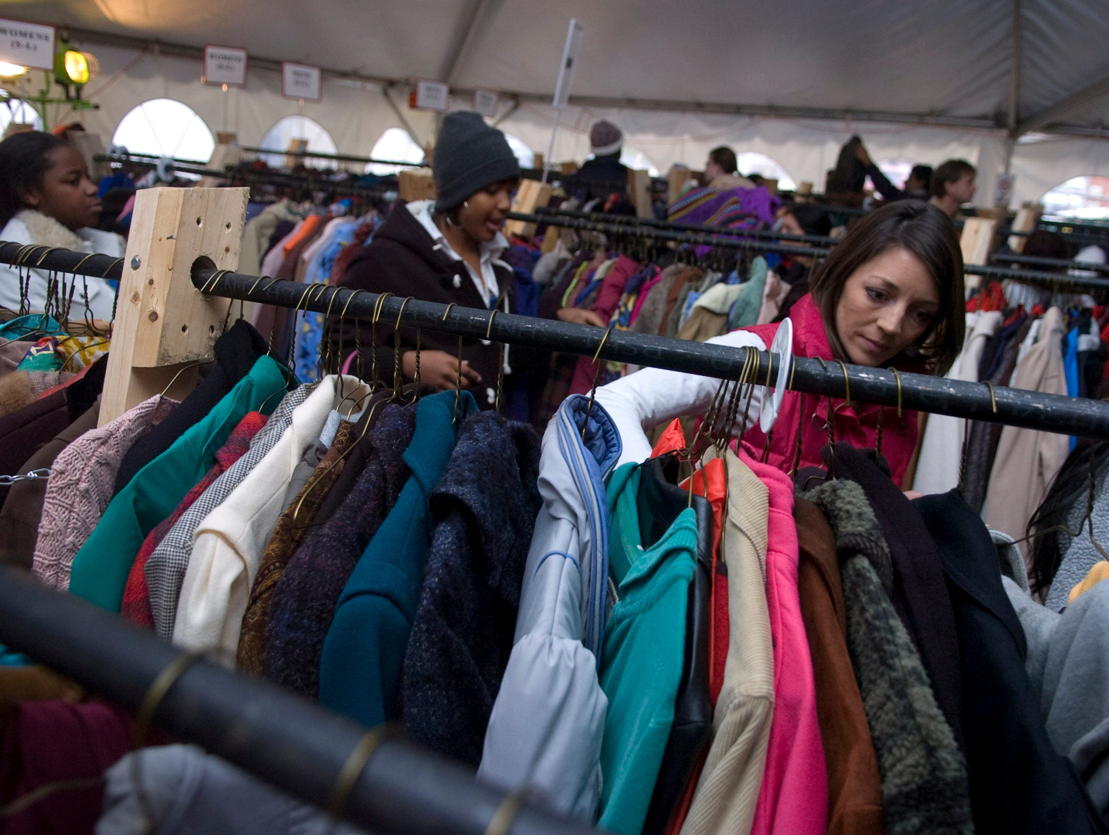 """Volunteer Kristen Slack helps a family to pick out coats at the Knoxville Area Rescue Ministries coat tent on Saturday, Dec. 4, 2010. The 25th anniversary of the annual """"Coats for the Cold"""" offered free coat distribution to any needy individual in the East Tennessee area. As many as 2,000 people received the 8,000 coats collected at the KARM Thrift Store at 733 Hall of Fame Drive. Each coat was cleaned free of charge by Prestige Cleaners."""