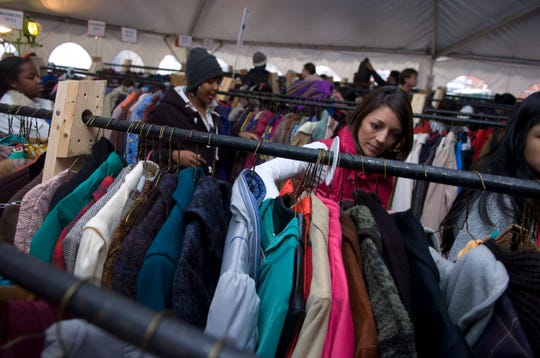 "Volunteer Kristen Slack helps a family to pick out coats at the Knoxville Area Rescue Ministries coat tent on Saturday, Dec. 4, 2010. The 25th anniversary of the annual ""Coats for the Cold"" offered free coat distribution to any needy individual in the East Tennessee area. As many as 2,000 people received the 8,000 coats collected at the KARM Thrift Store at 733 Hall of Fame Drive. Each coat was cleaned free of charge by Prestige Cleaners."