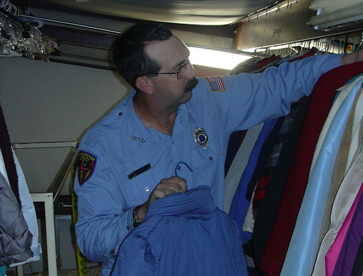 Johnny Leatherwood of the Blount County Fire Department arranges garments donated for the Coats for the Cold drive.