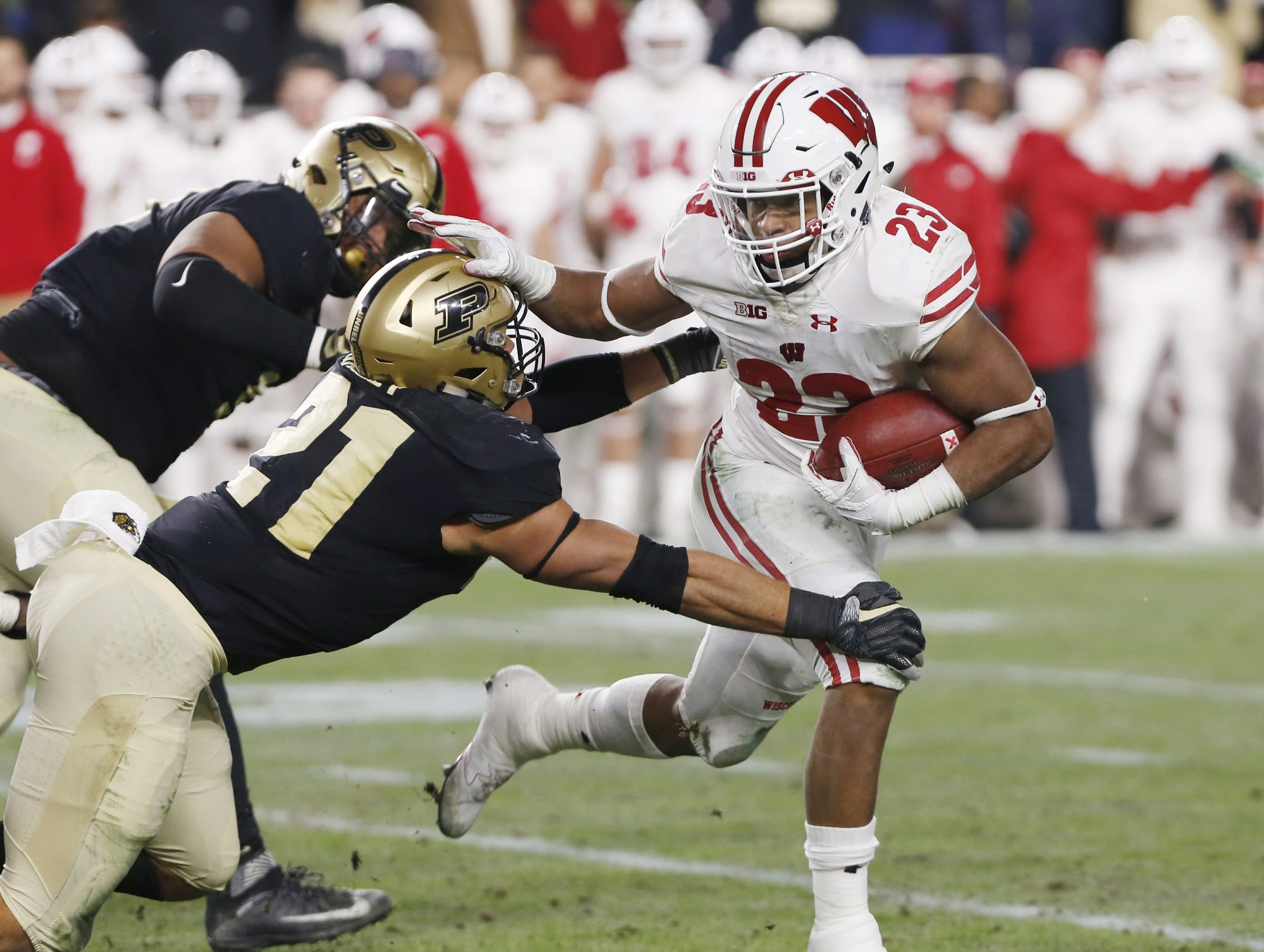 Jonathan Taylor of Wisconsin gets past Markus Bailey of Purdue on a second half carry Saturday, November 17, 2018, at Ross-Ade Stadium. Purdue fell to Wisconsin 47-44 3OT.