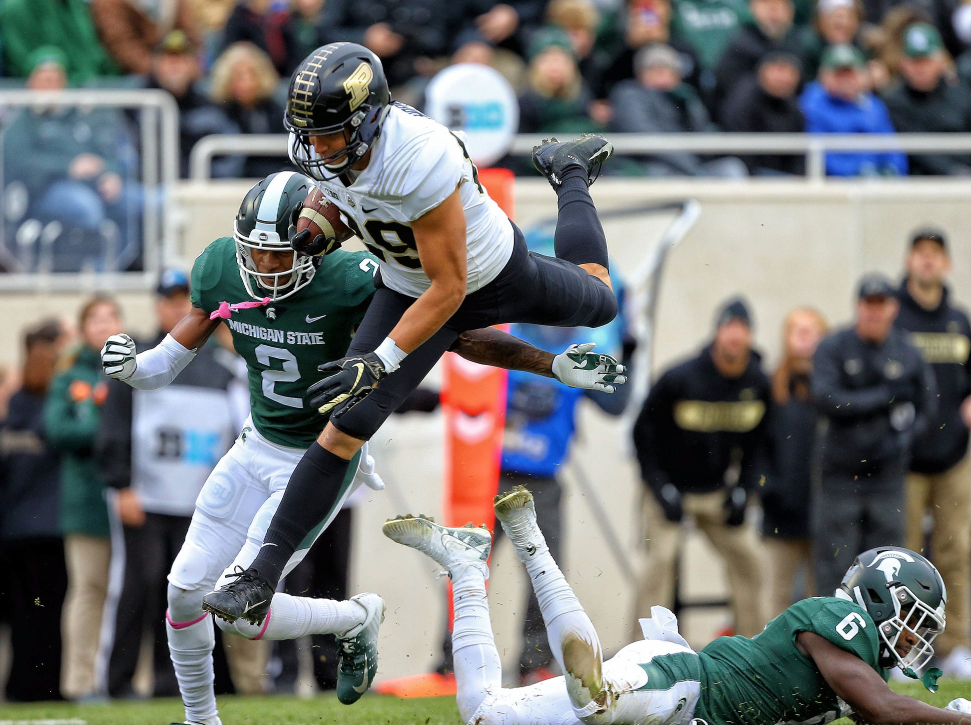 Purdue Boilermakers tight end Brycen Hopkins (89) hurdles Michigan State Spartans safety David Dowell (6) during the first quarter of a game at Spartan Stadium.