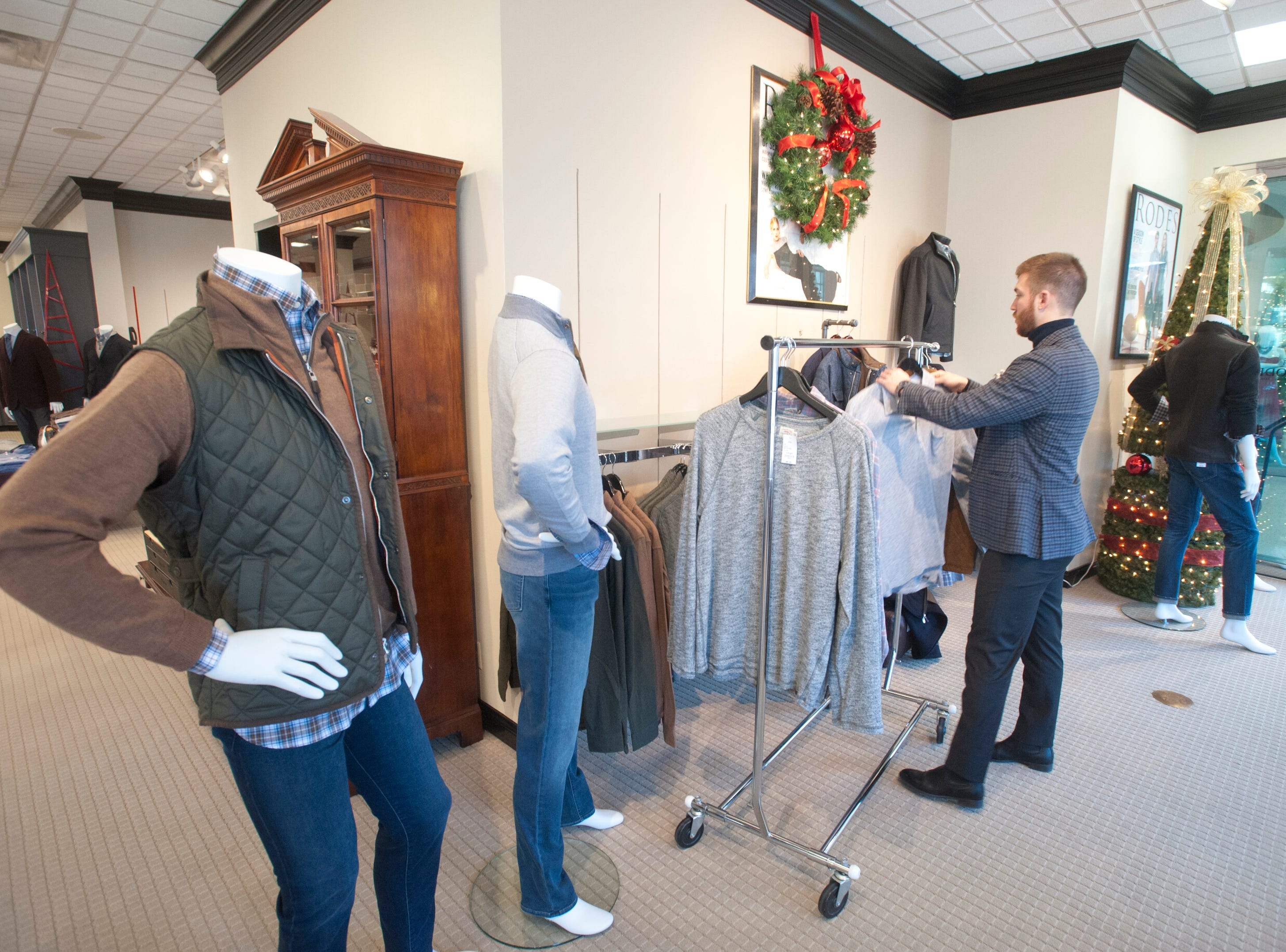 Rodes' men' stylist Chris Burns places sweaters on a rack at the Brownsboro Road store in Louisville. 