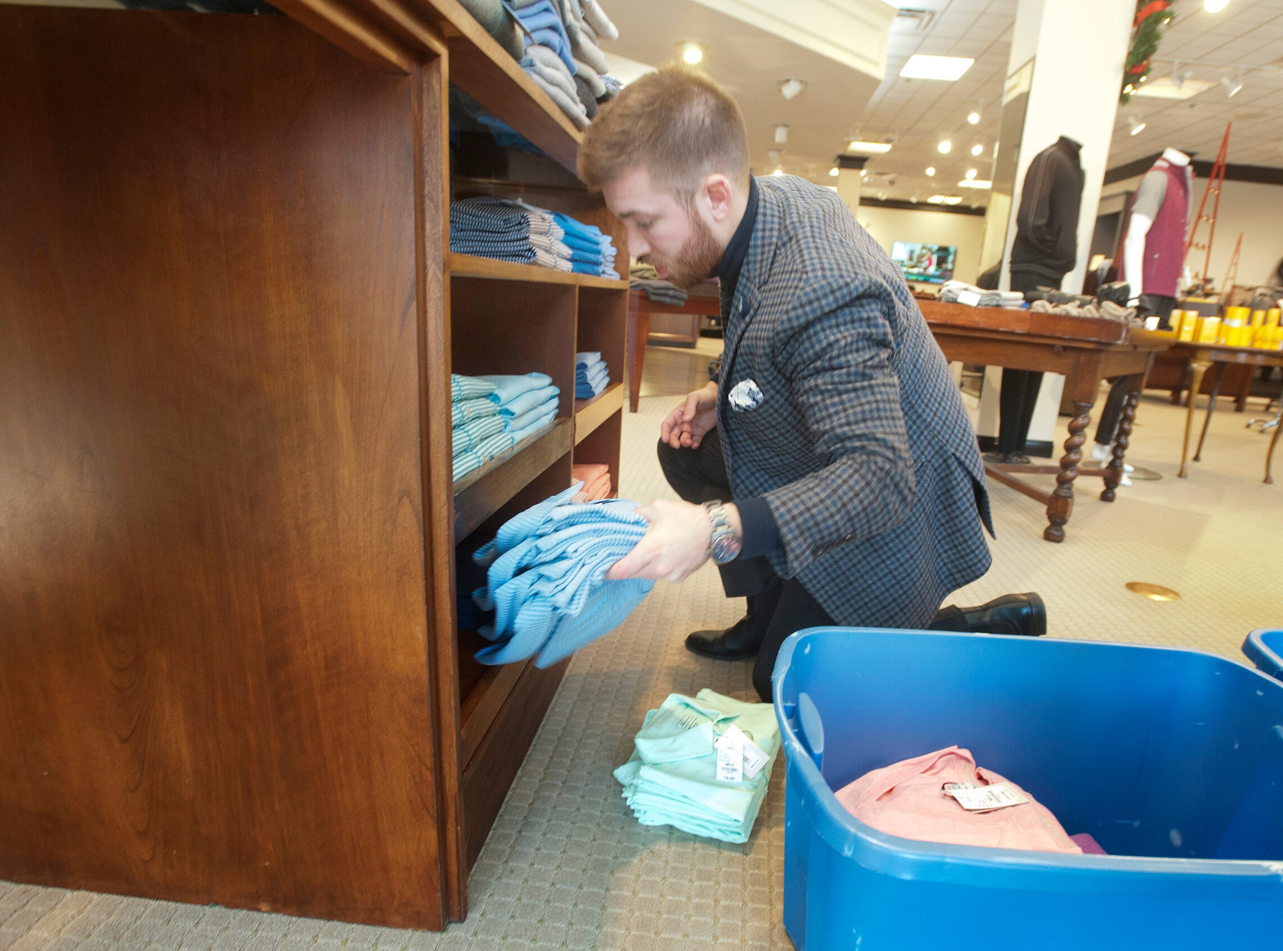 Rodes for Him men' stylist Chris Burns places shirts into a sales display at the Brownsboro Road store in Louisville. 