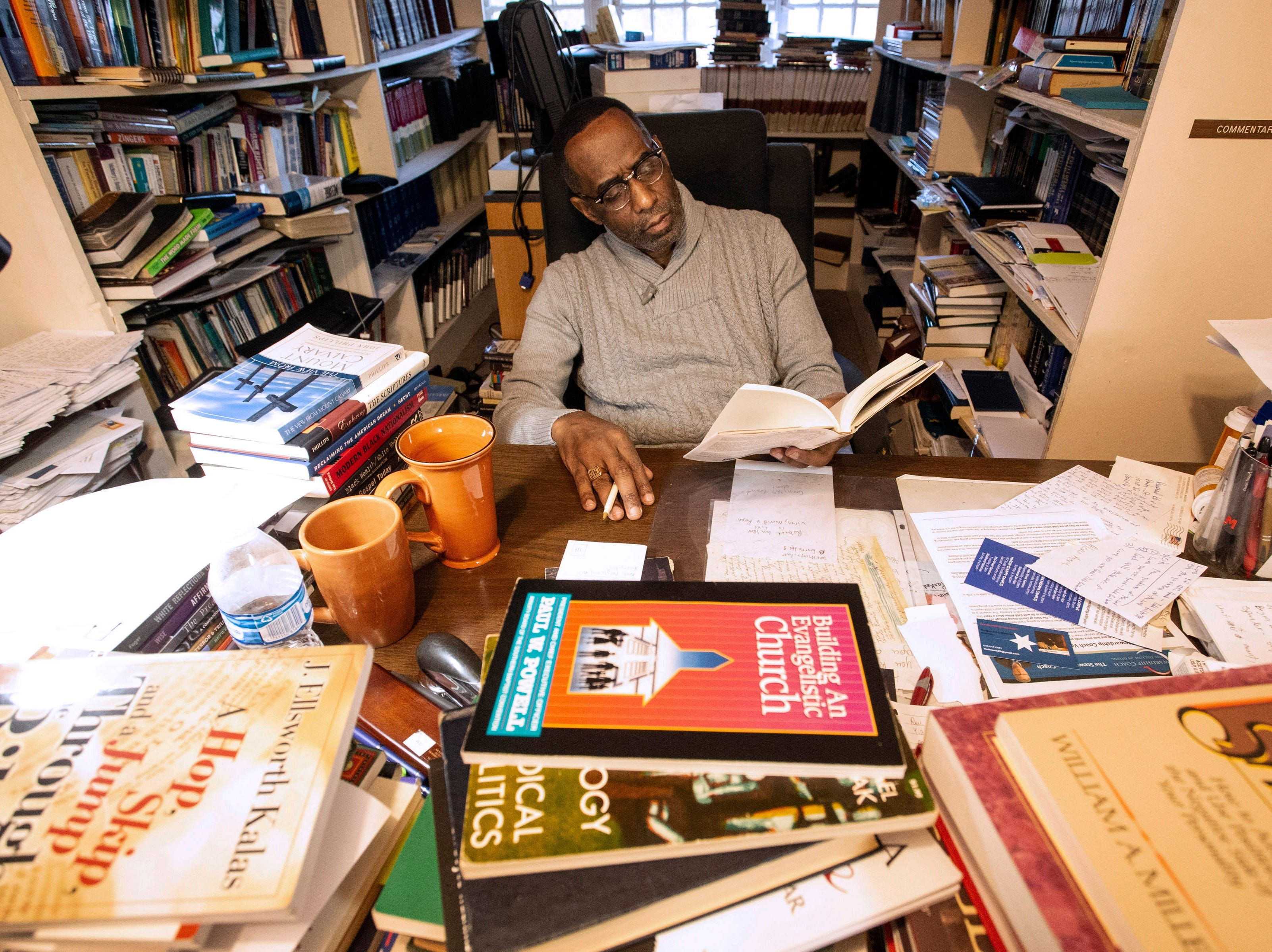 A desk nestled between shelves and stacks of books is where the Reverend Kevin Cosby does his sermon writing. 11/24/18