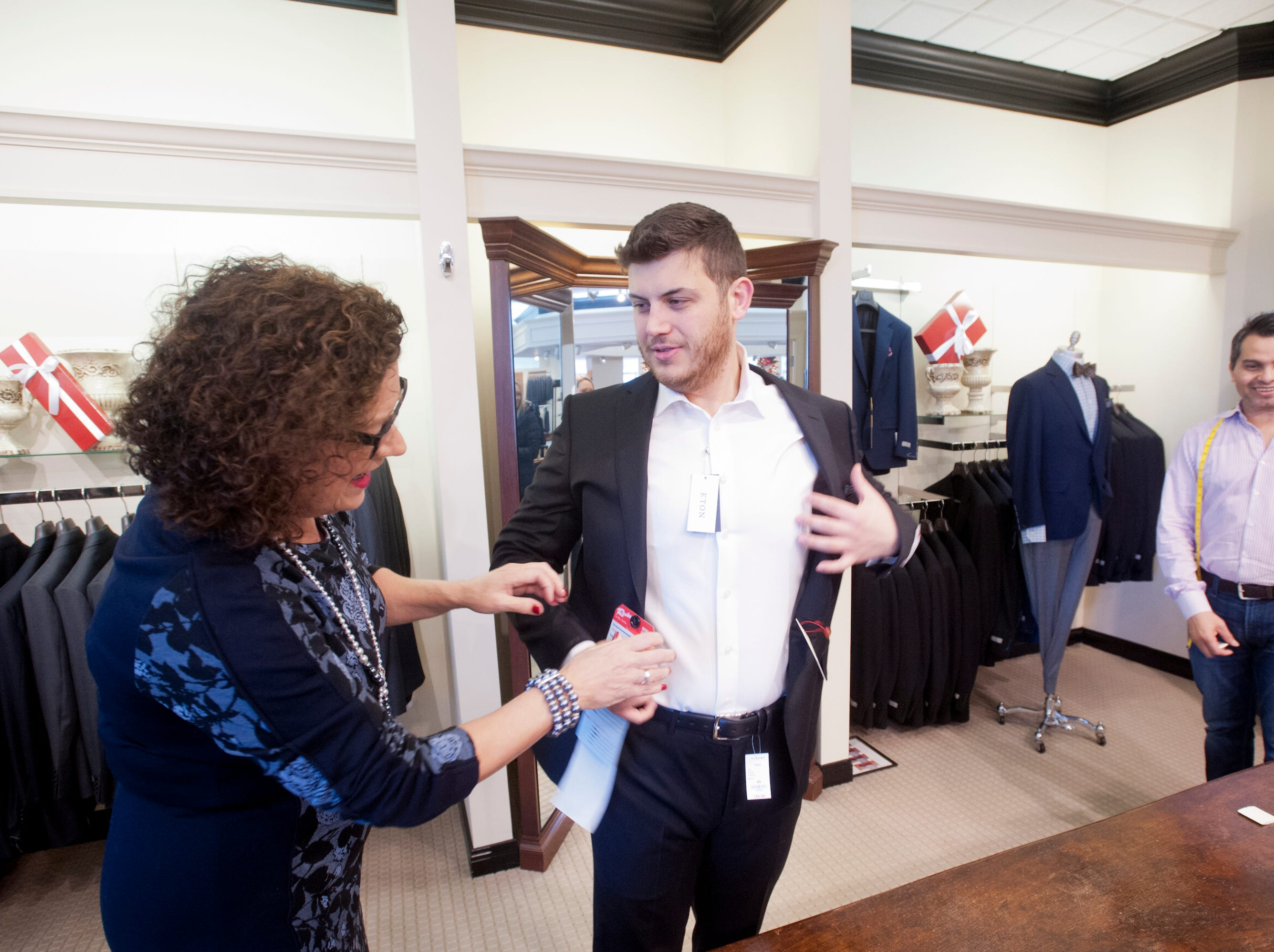 Morgan Davis, of Sydney, Australia, is helped into a suit by Rodes clothing consultant Cheri Hines, left, as store tailor David Amaya, right, waits to step in for a measure.