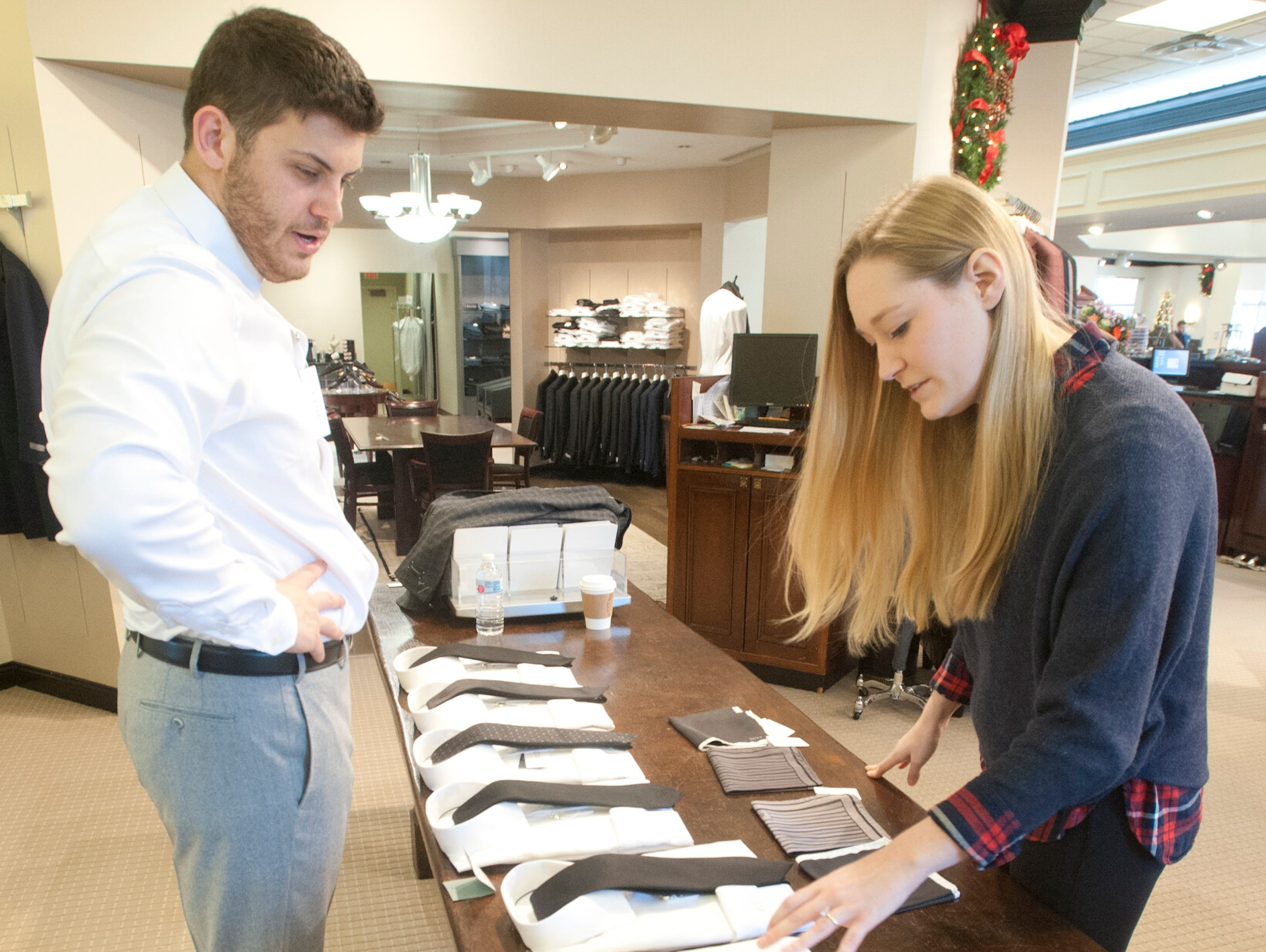 Morgan Davis and his fiancee Violet Downs select  ties and pocket scarves at the Rodes for Men store on Brownsboro Road. The couple, who plan to marry on December 29th, were in the store pick out clothes for him and for his groomsmen. This is the 5th generation of Davis' family to shop at Rodes.