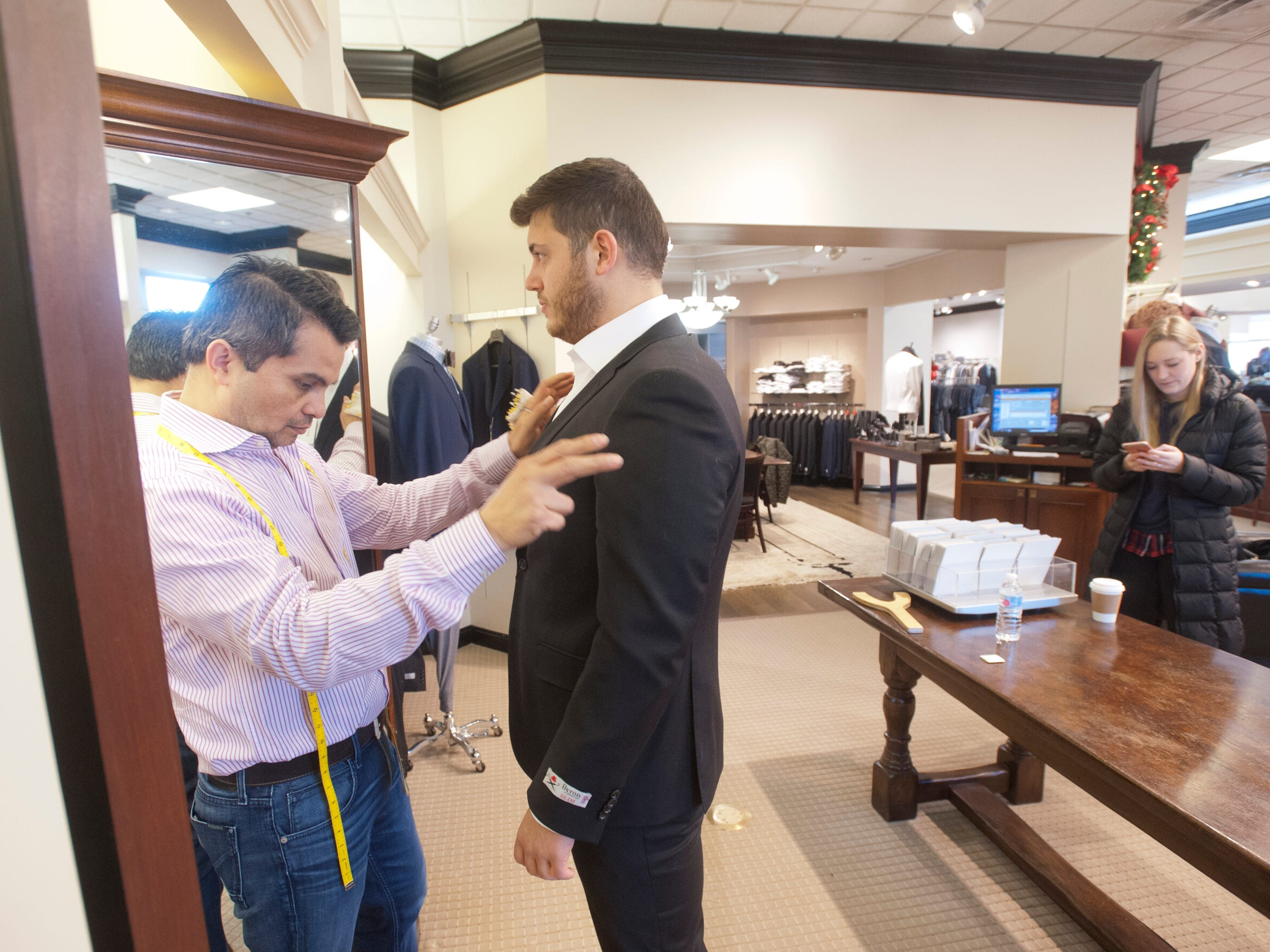Rodes store tailor David Amaya fits Morgan Davis, of Sydney, Australia, for a suit as Davis' fiancee, Violet Downs of Bardstown, texts to a friend. The wedding is set for December 29th.