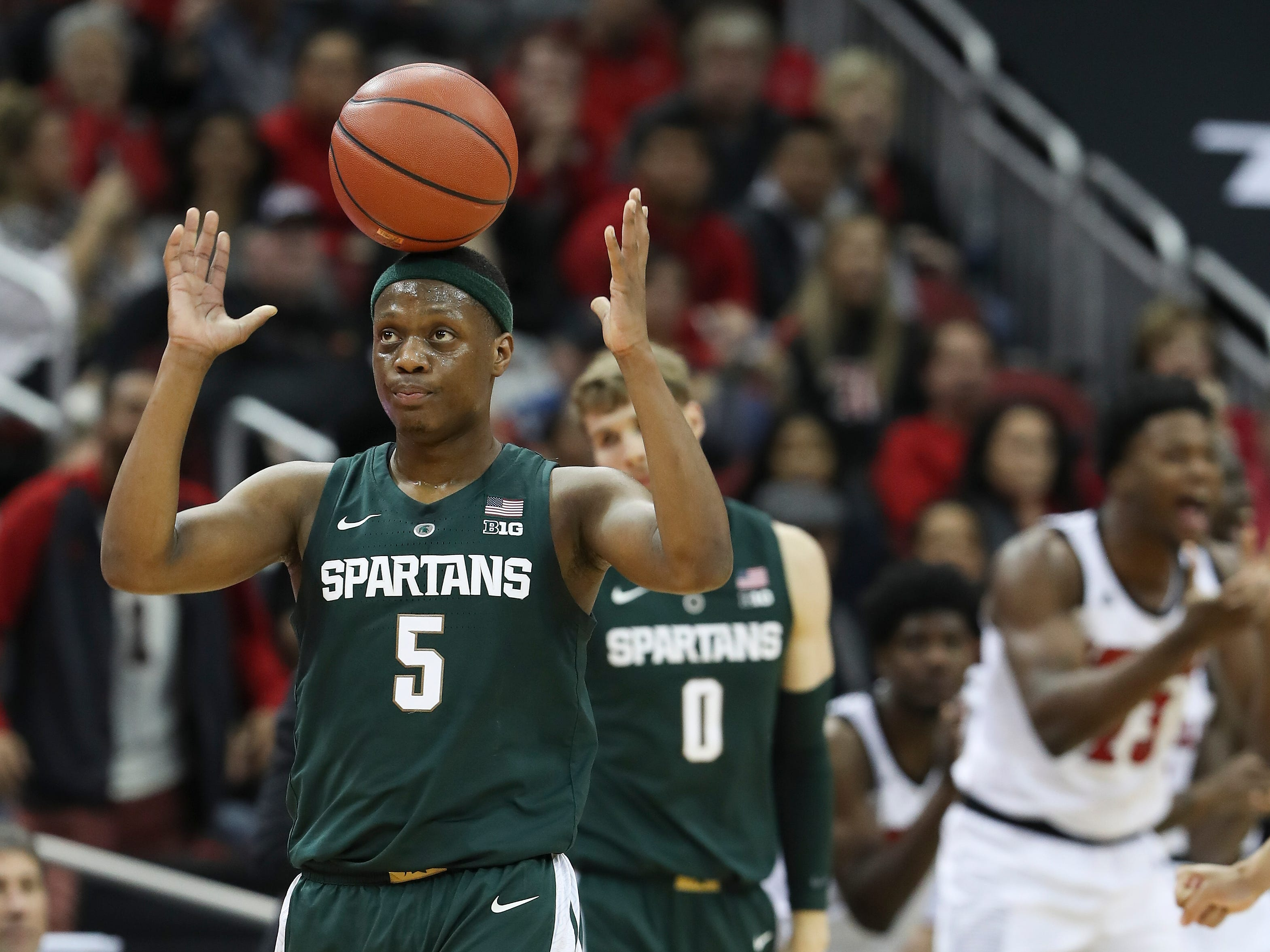 Michigan State's Cassius Winston let the ball balance on his head after a ref made a call against the Spartans during against Louisville, Nov. 27, 2018