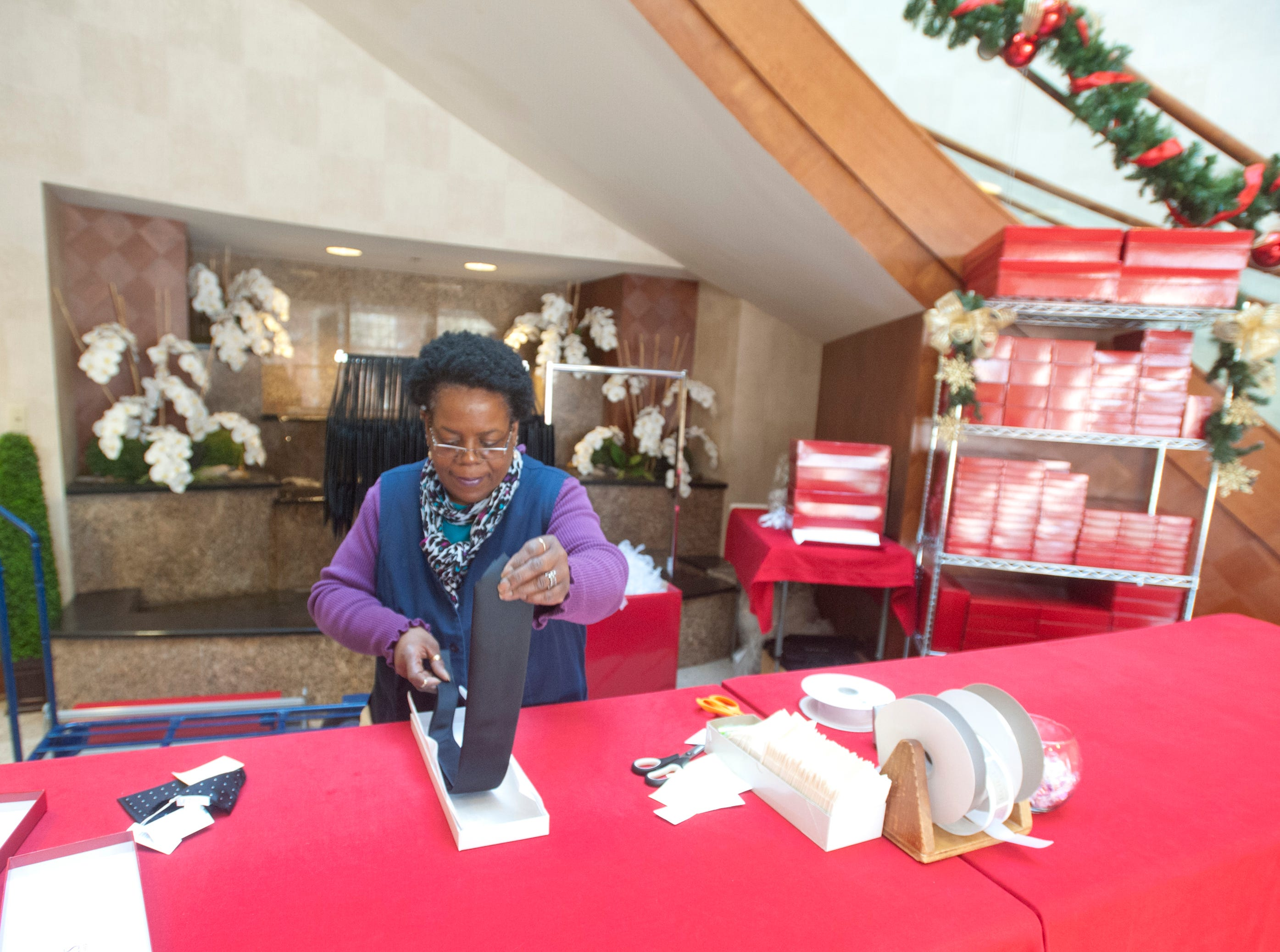 Charlene Dunlap, a shipping and receiving manager for Rodes on Brownsboro Road in Louisville, packages a tie before decorating the box a holiday wrapping station between the Rodes for Men and Rodes for Women stores.