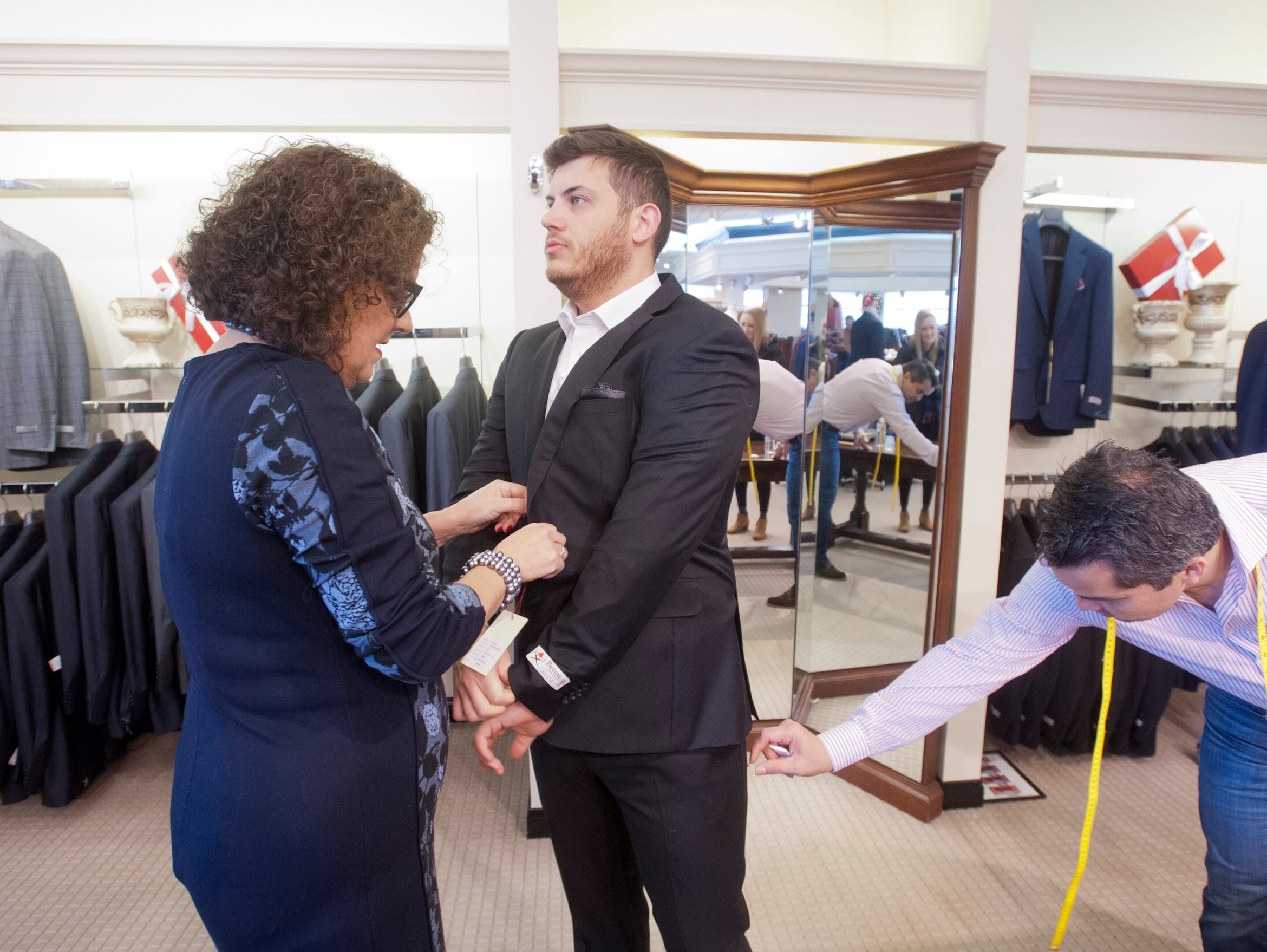 Morgan Davis, of Sydney, Australia, is helped into a suit by Rodes clothing consultant Cheri Hines, left, as store tailor David Amaya, right, pulls a tag from the suit. Davis is planning to wed his fiancee, Violet Downs of Bardstown, on December 29th.