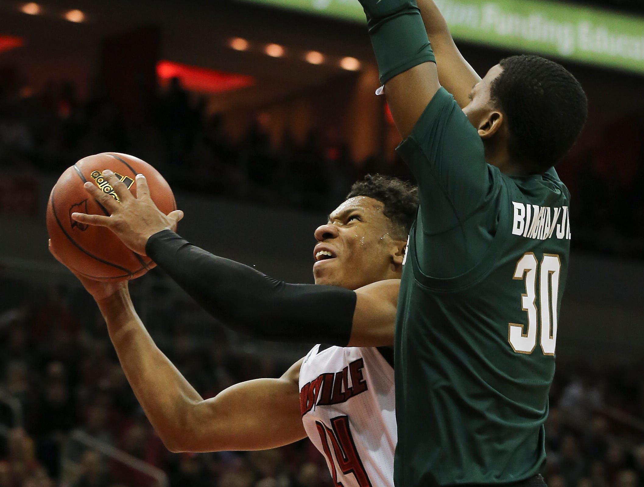 Louisville's Dwayne Sutton (24) shoots over Michigan State's Marcus Bingham Jr. (30) during their game at the Yum Center.   Nov. 27, 2018