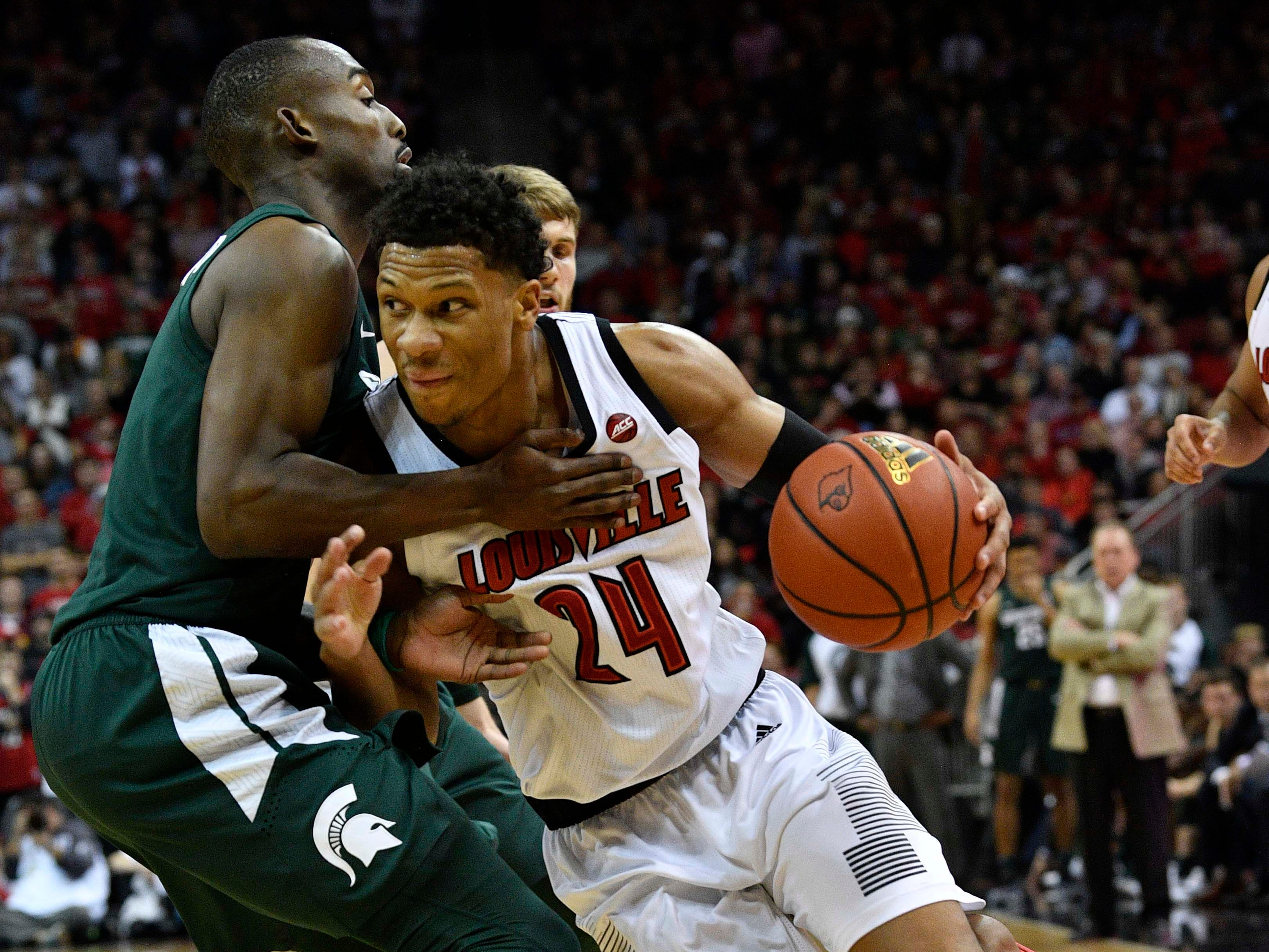 Louisville Cardinals forward Dwayne Sutton (24) dribbles against Michigan State Spartans guard Joshua Langford (1) during the second half at KFC Yum! Center. Louisville defeated Michigan State 82-78.