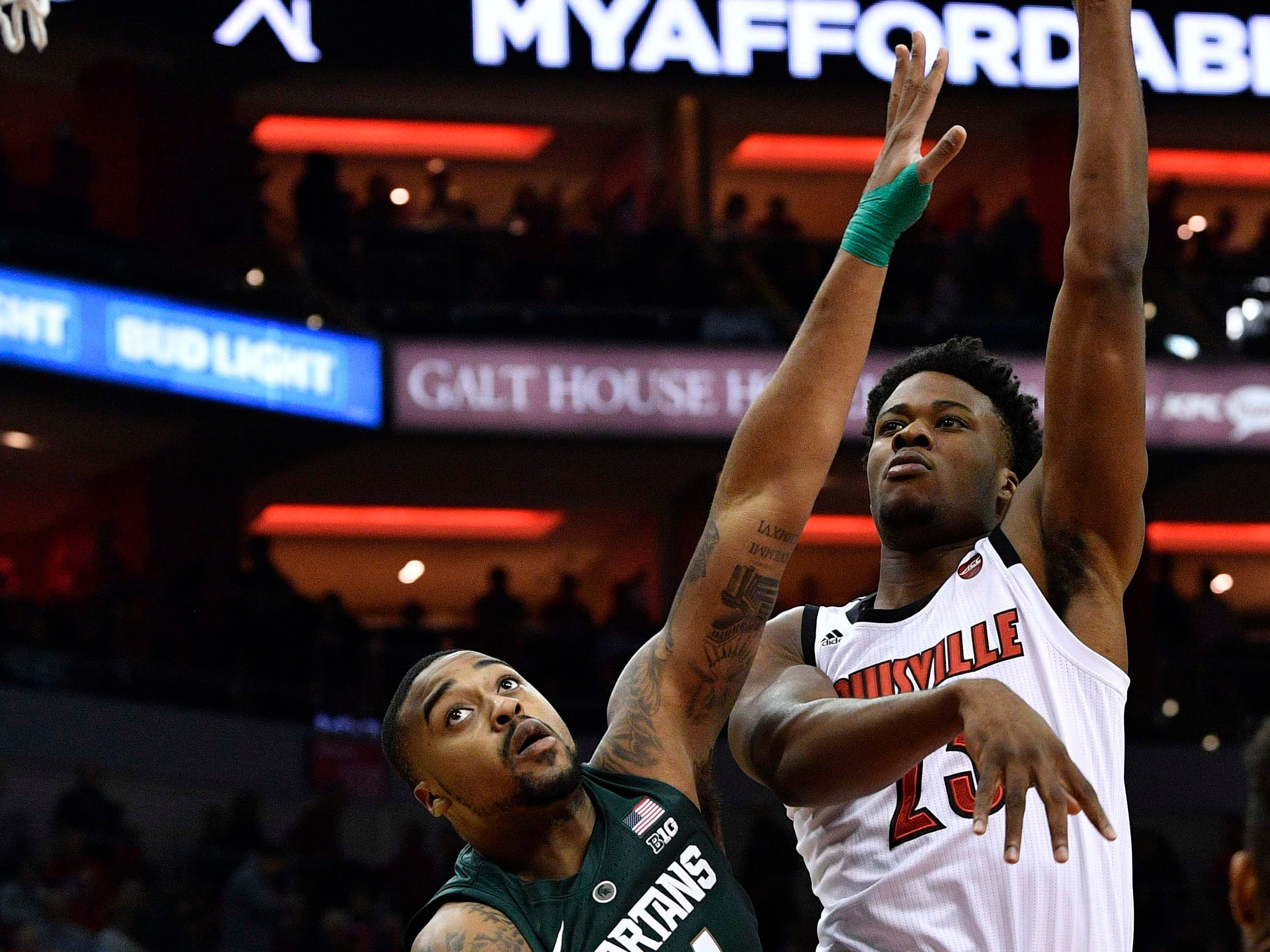 Louisville Cardinals center Steven Enoch (23) shoots against Michigan State Spartans forward Nick Ward (44) during the second half at KFC Yum! Center. Louisville defeated Michigan State 82-78.